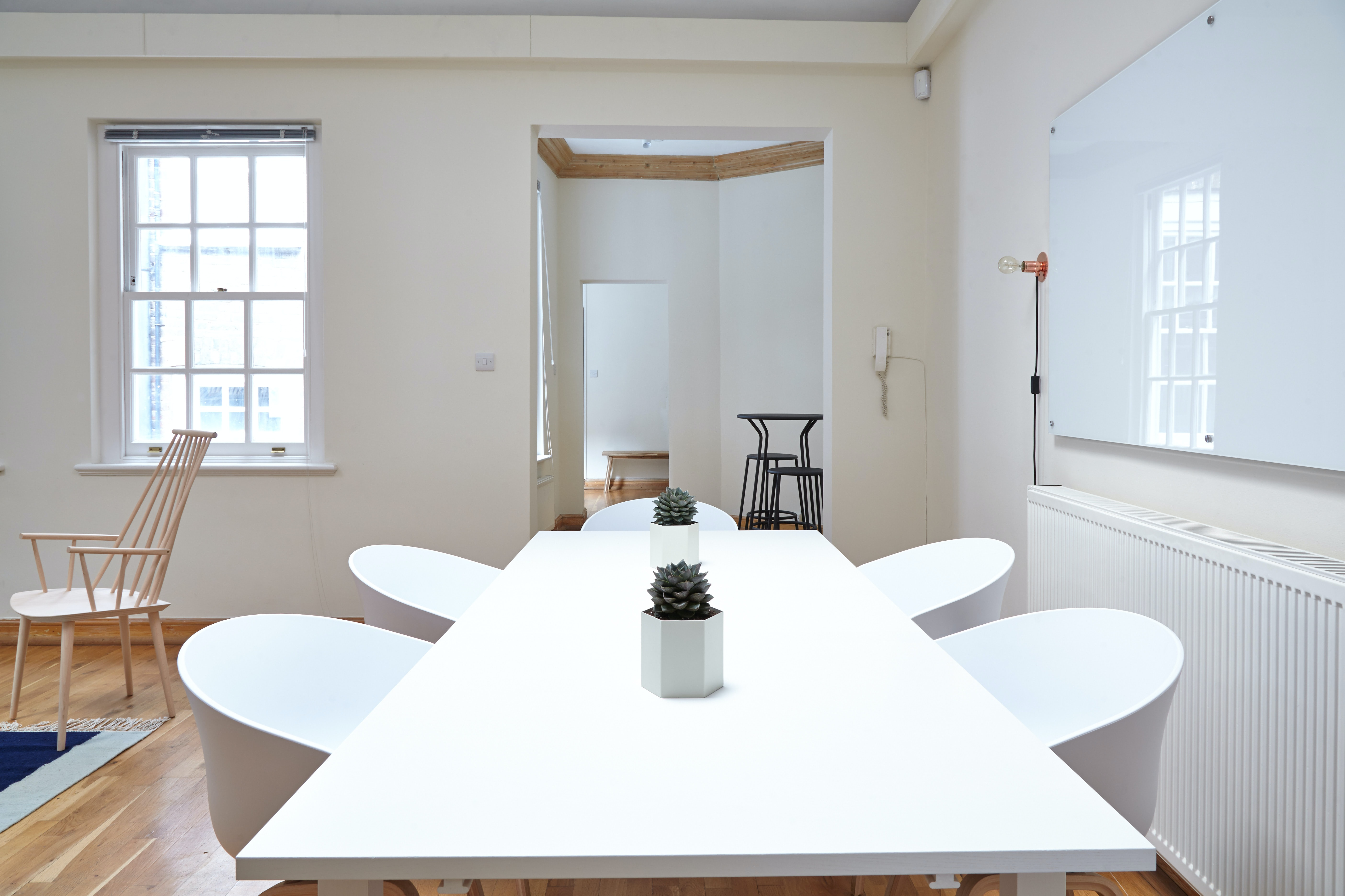 An office space with a white table and a whiteboard on a wall