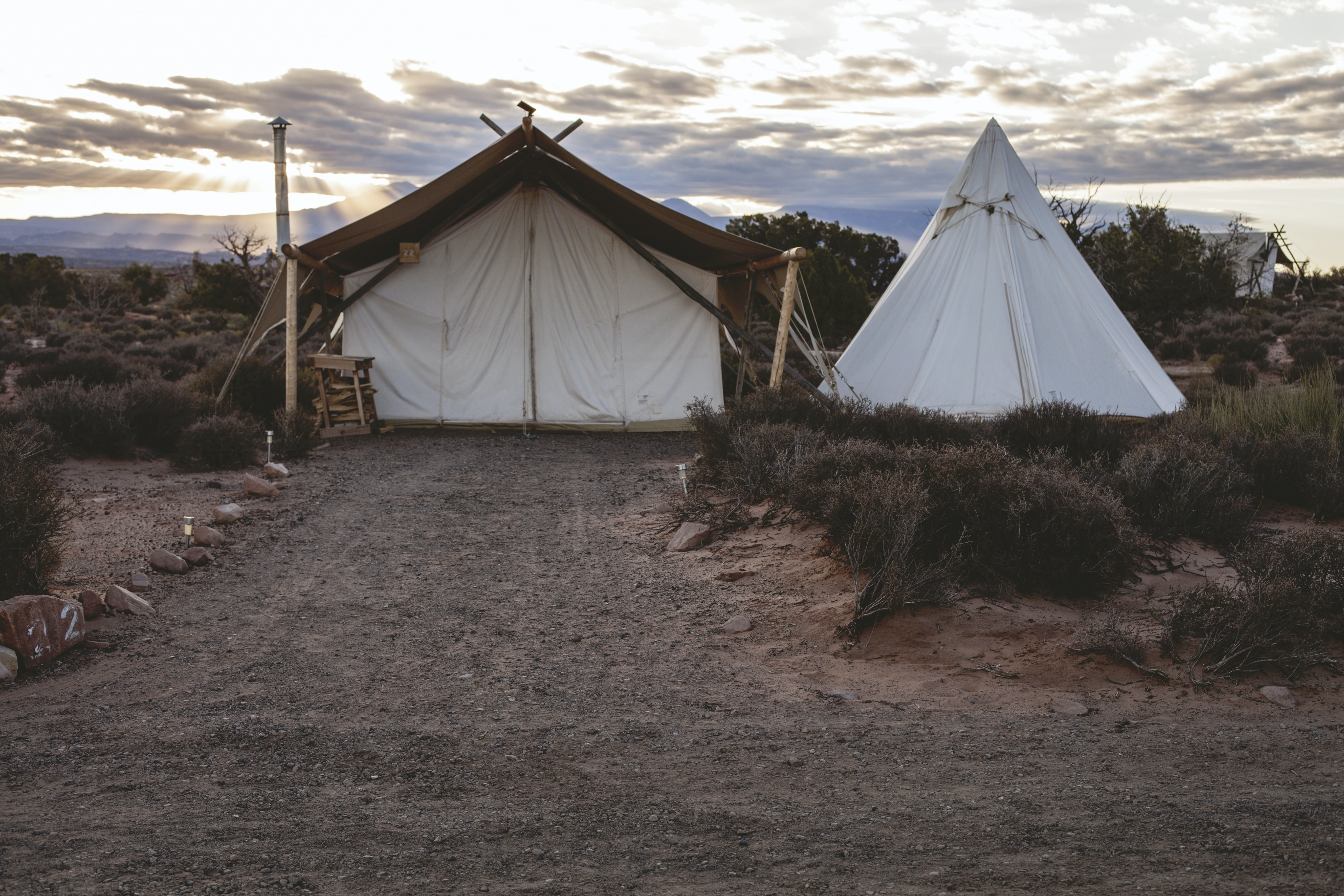 Rural campsite with a tent and teepee in a barren landscape