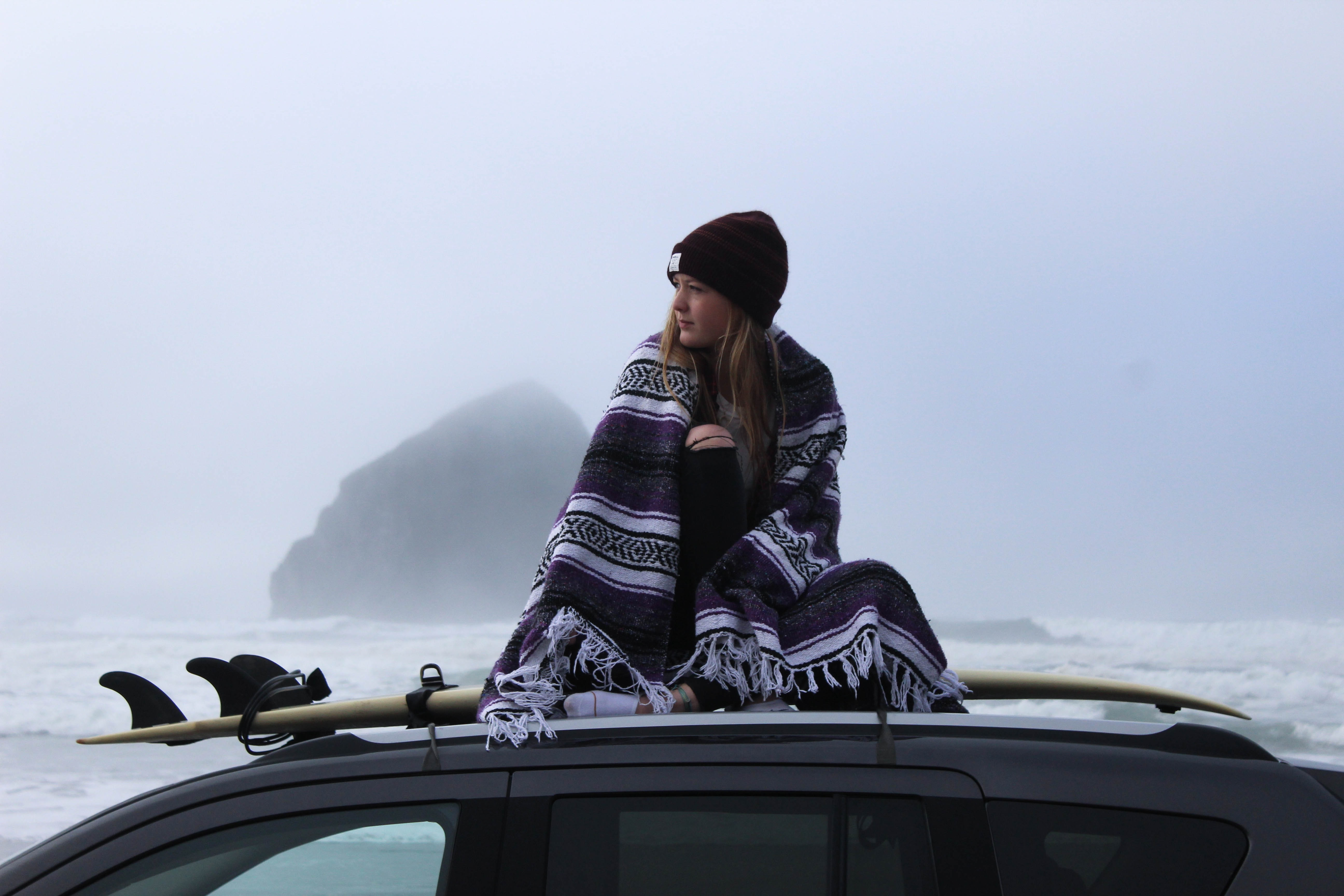 Woman wrapped up in a blanket sitting on a car roof by the surfboard at Cannon Beach