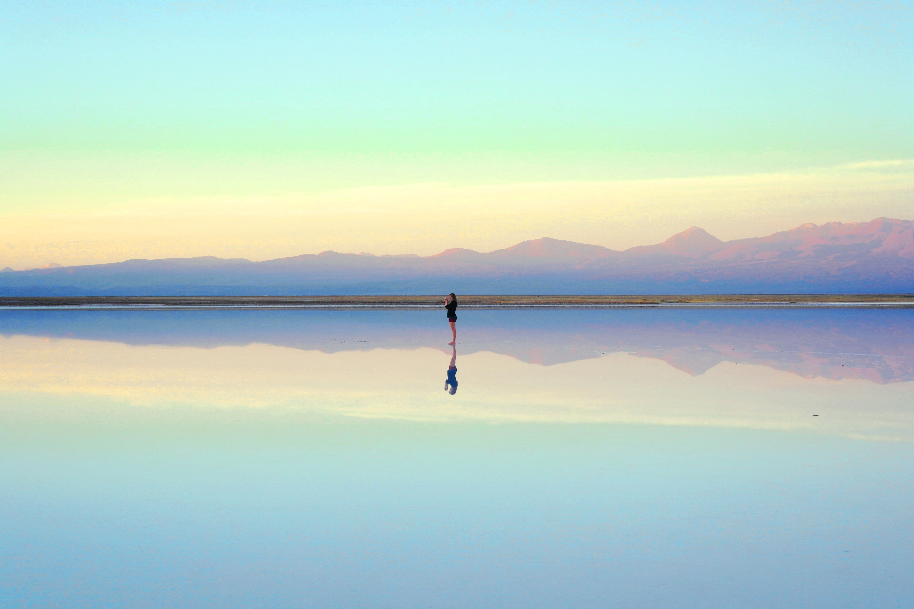 An optic illusion featuring a woman standing on the mirror-like surface of pale blue water