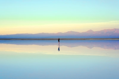 person standing near body of water during daytime reflection teams background