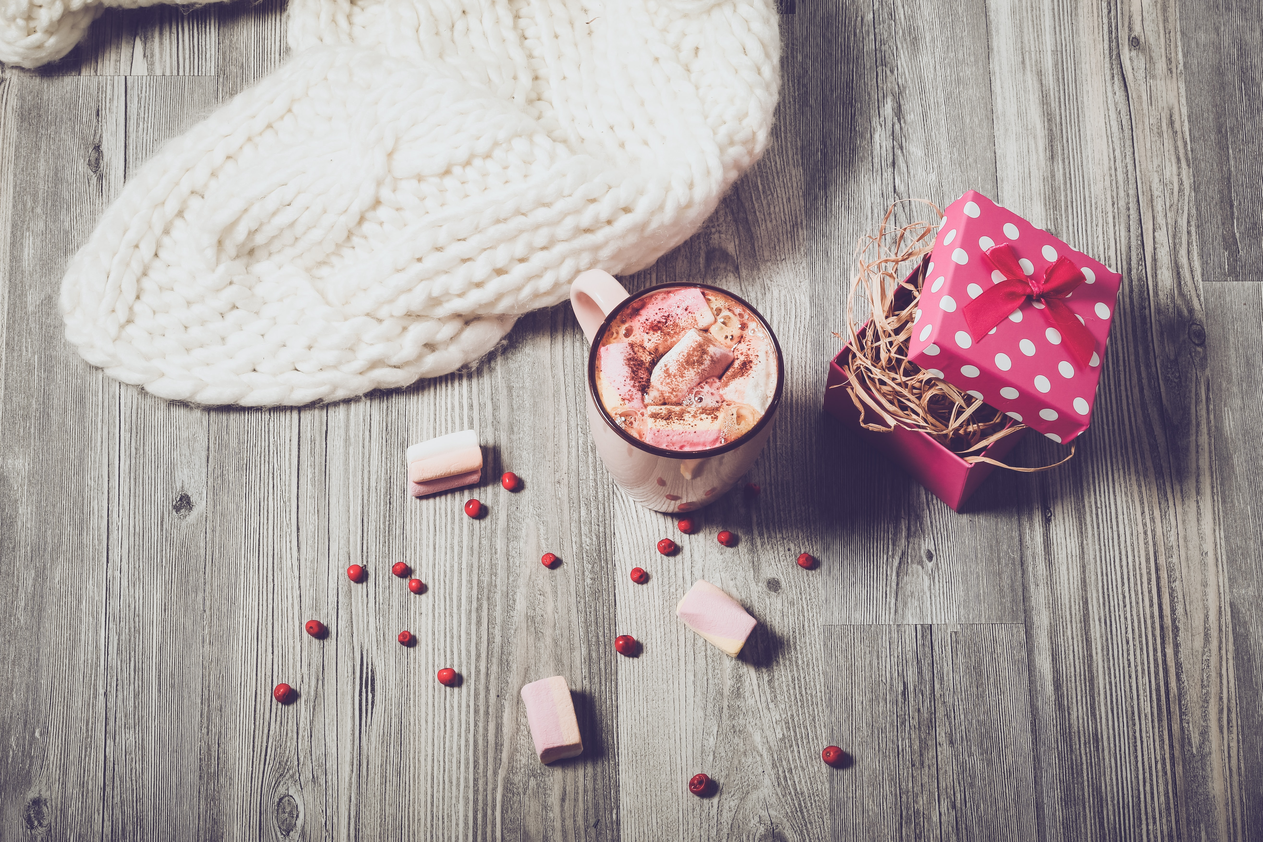 A hot beverage surrounded by berries, a knitted item and a gift wrapped box containing straw.