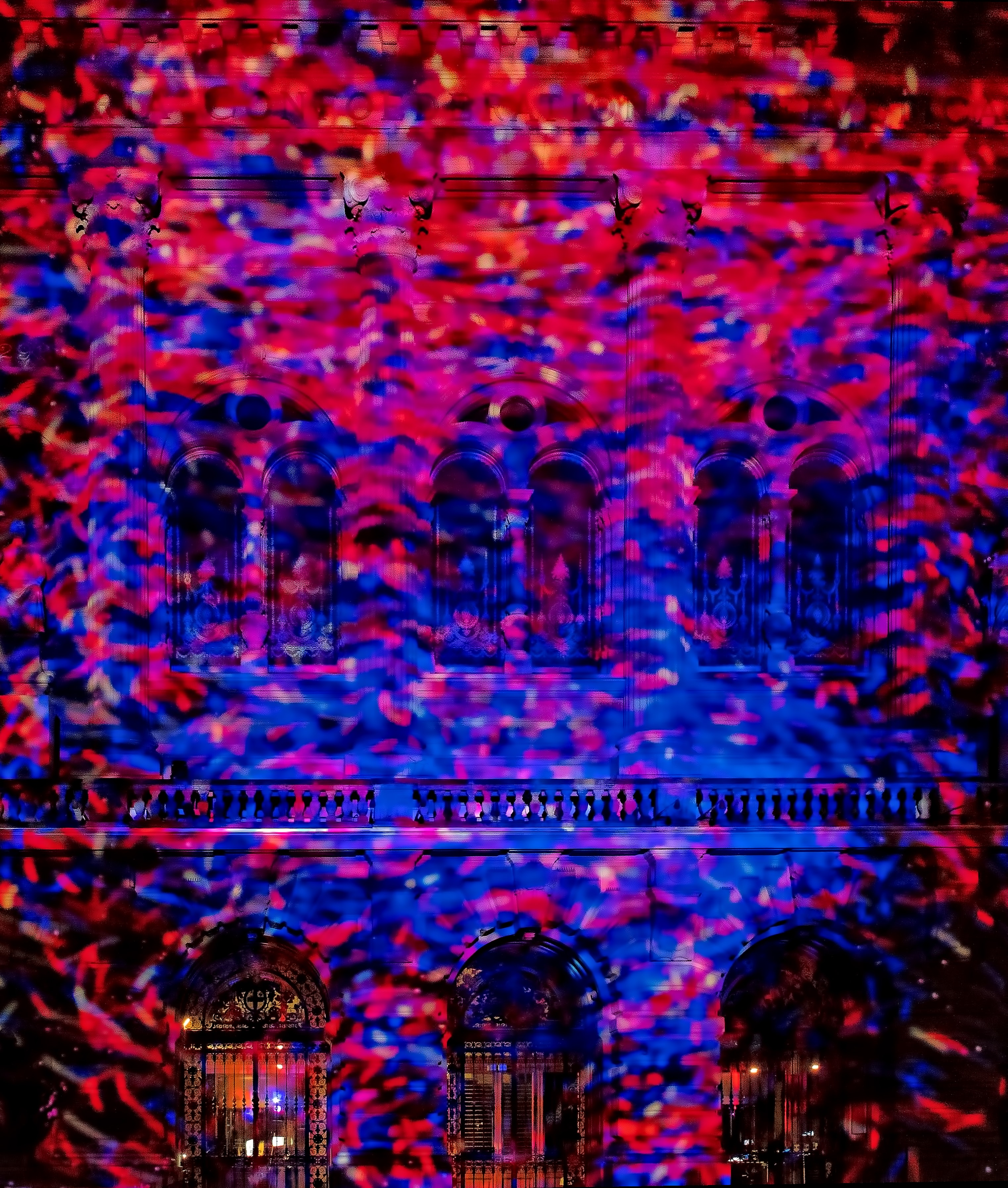 Red and blue spotlights vividly shining onto a building.