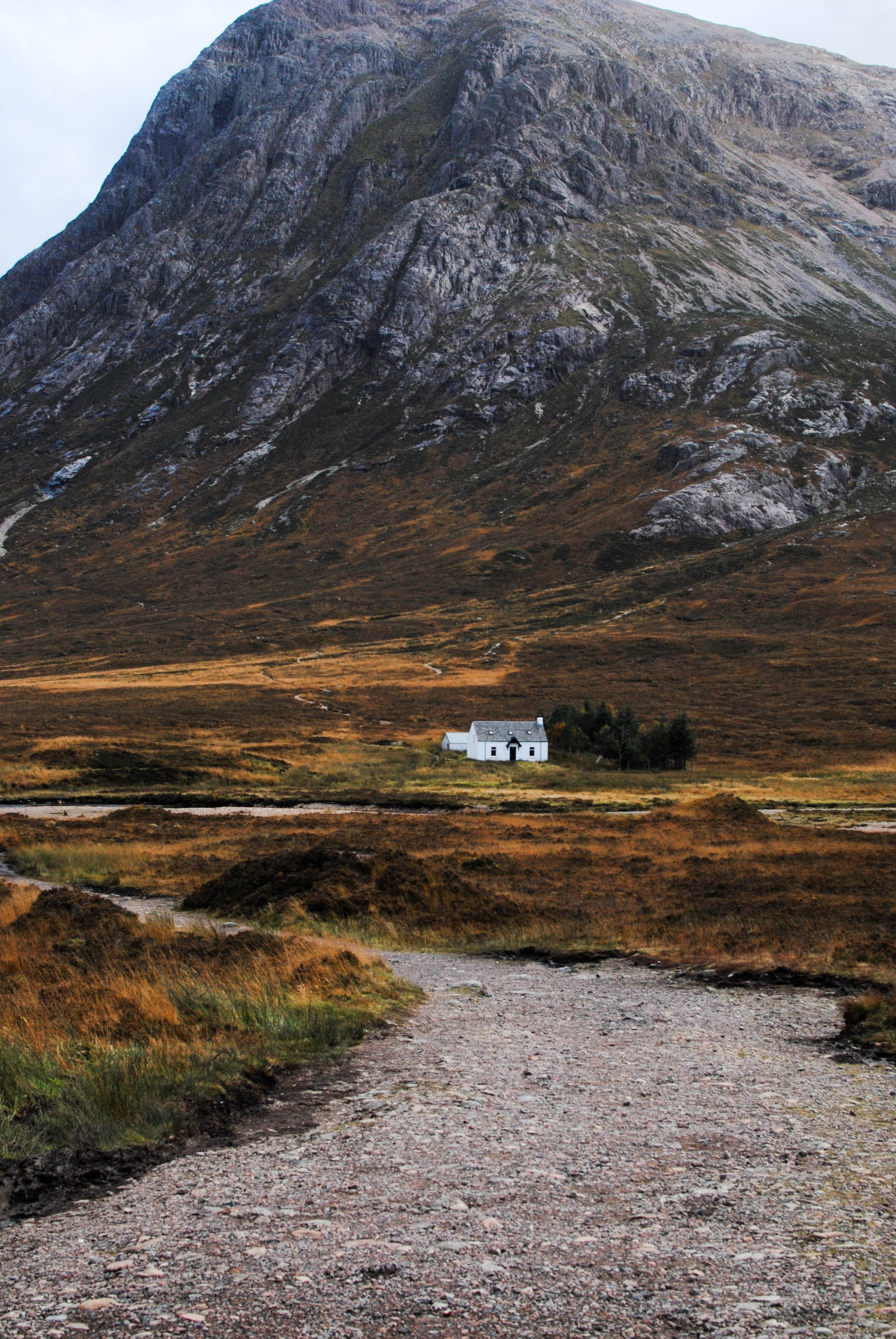 A small white building on a grassy plain at a rugged mountain's foot