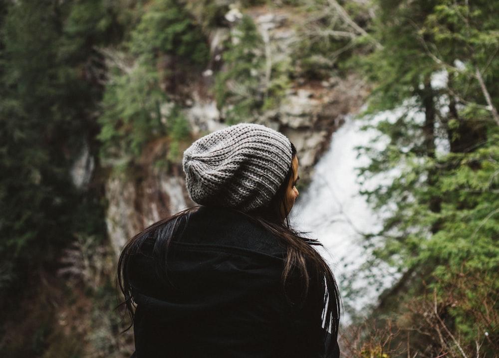 woman in black coat standing near mountain