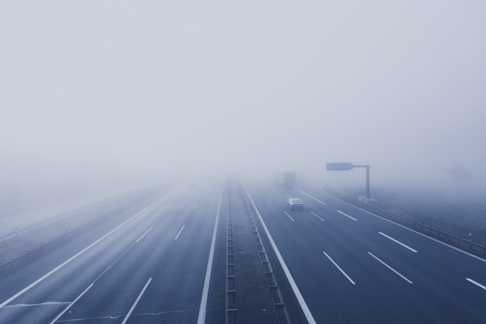 road passing by in road while fogging