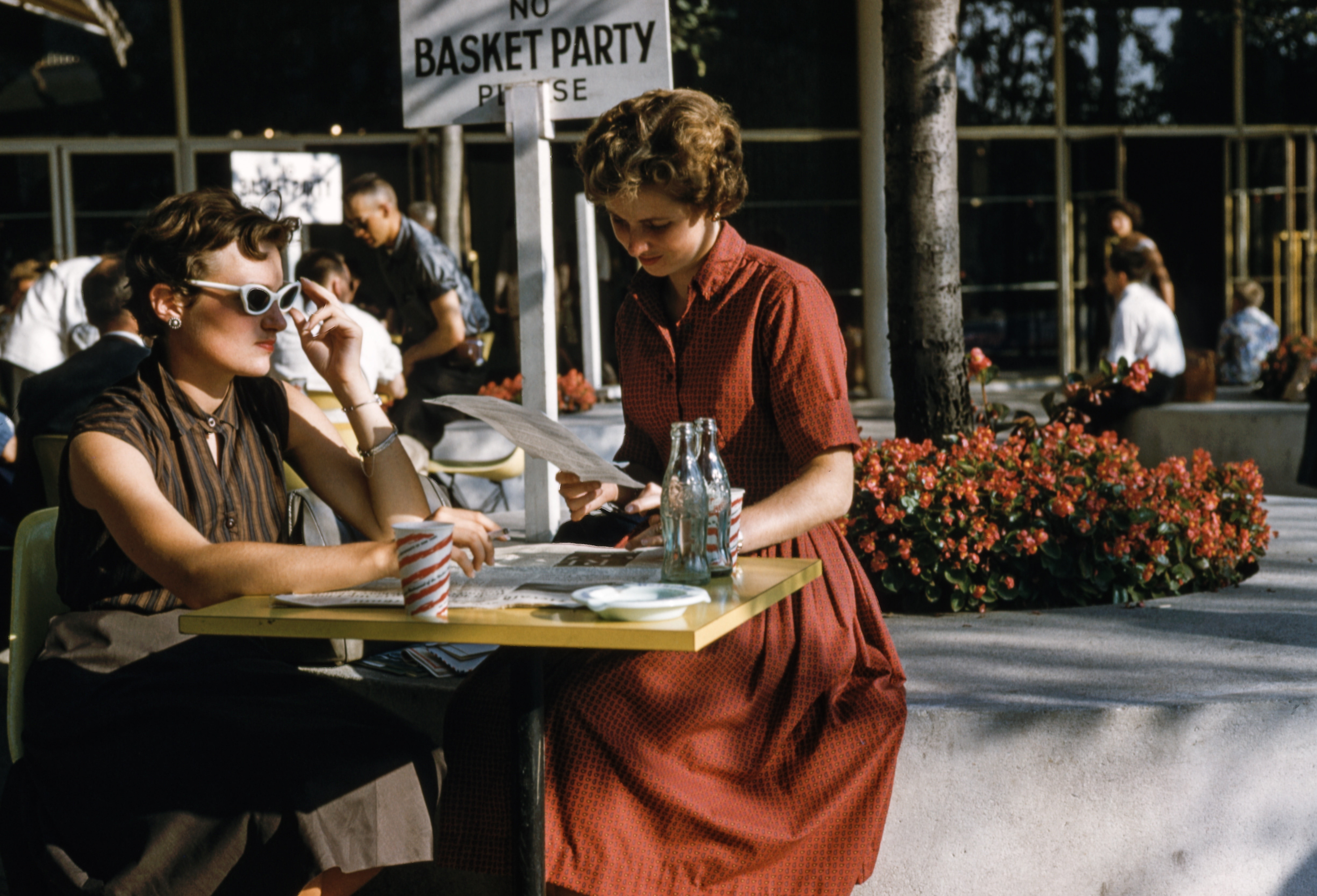 A vintage photograph of two women sitting at a cafe table.