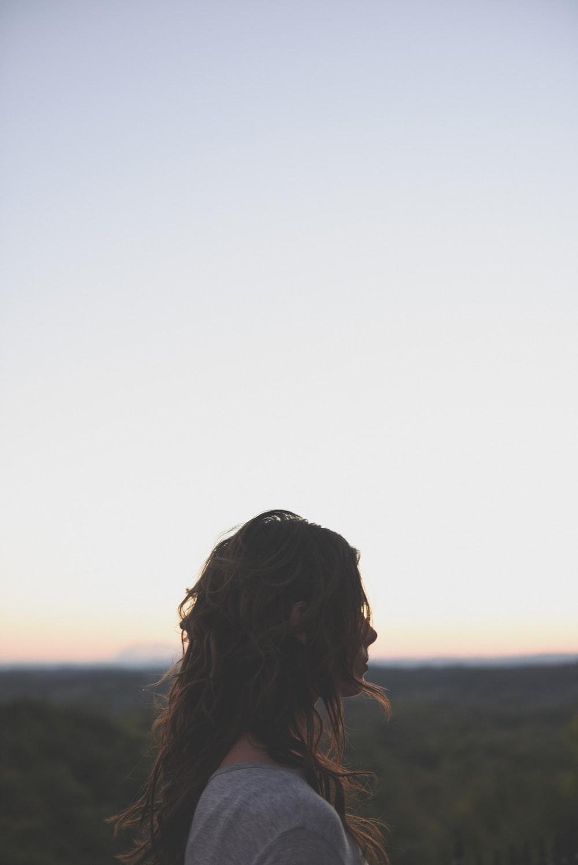 brunette hair woman wearing gray top looking side way