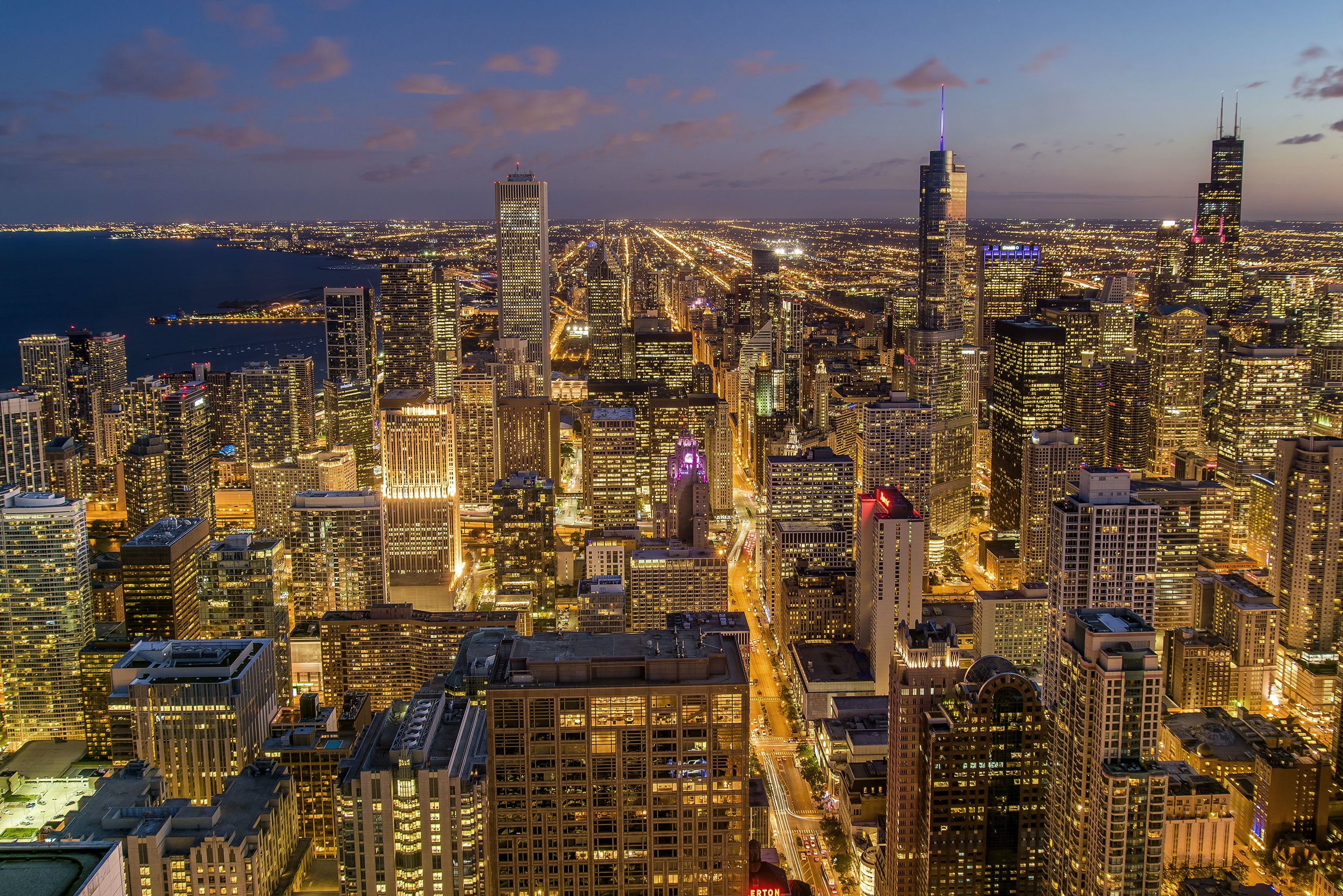 A cityscape of chicago with bright lights and neons on an evening
