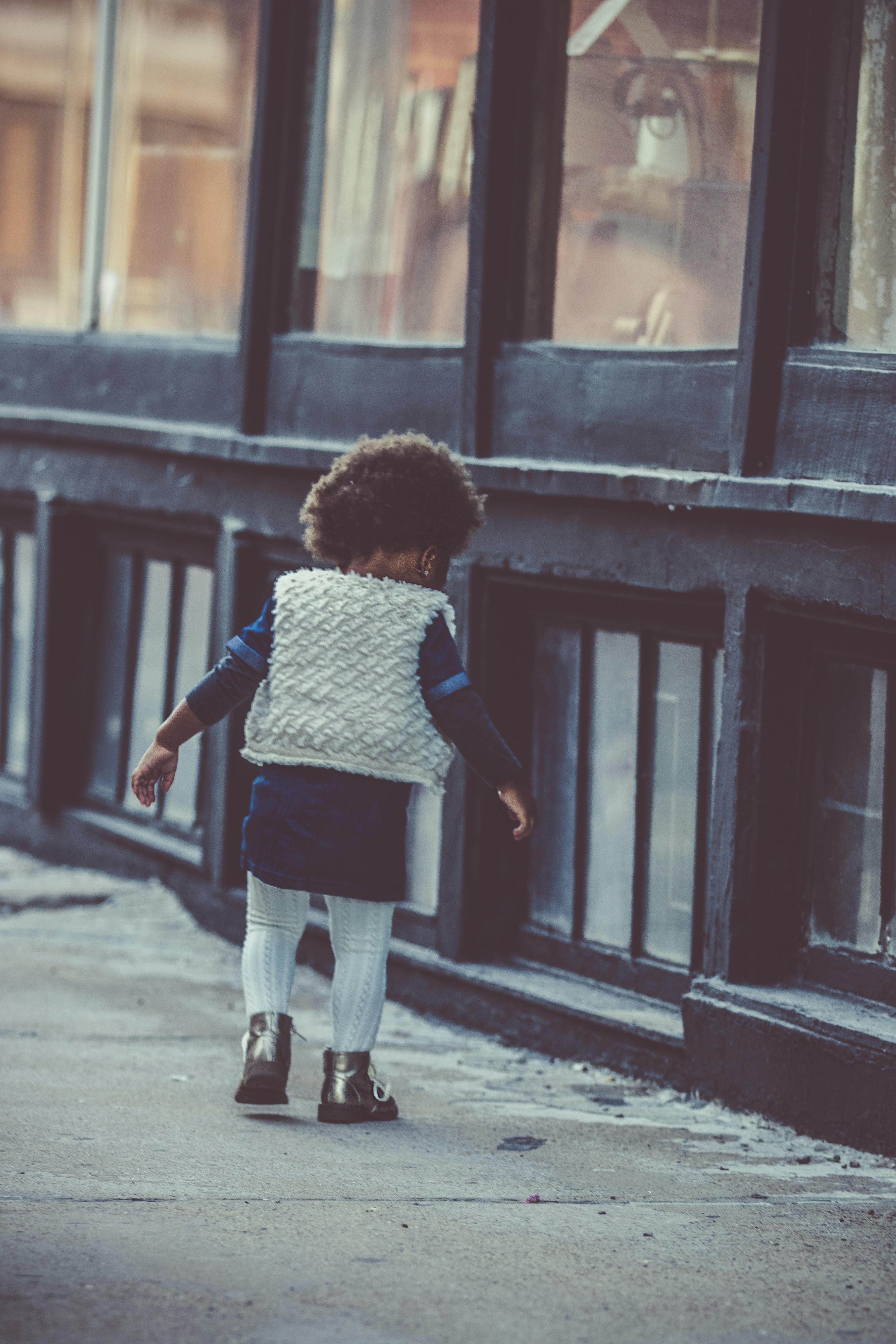 A kid walking down the street.