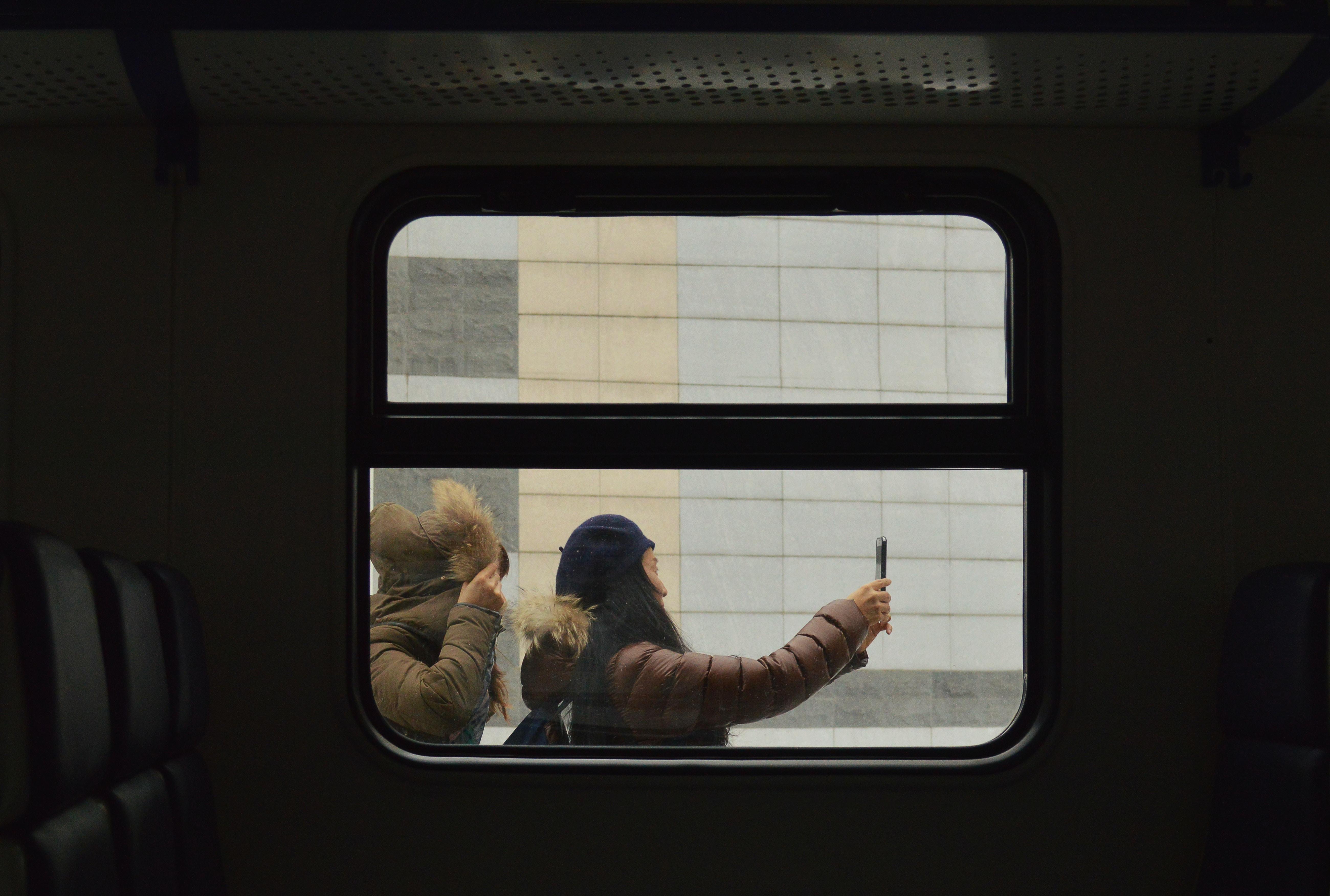 woman taking photo outside train