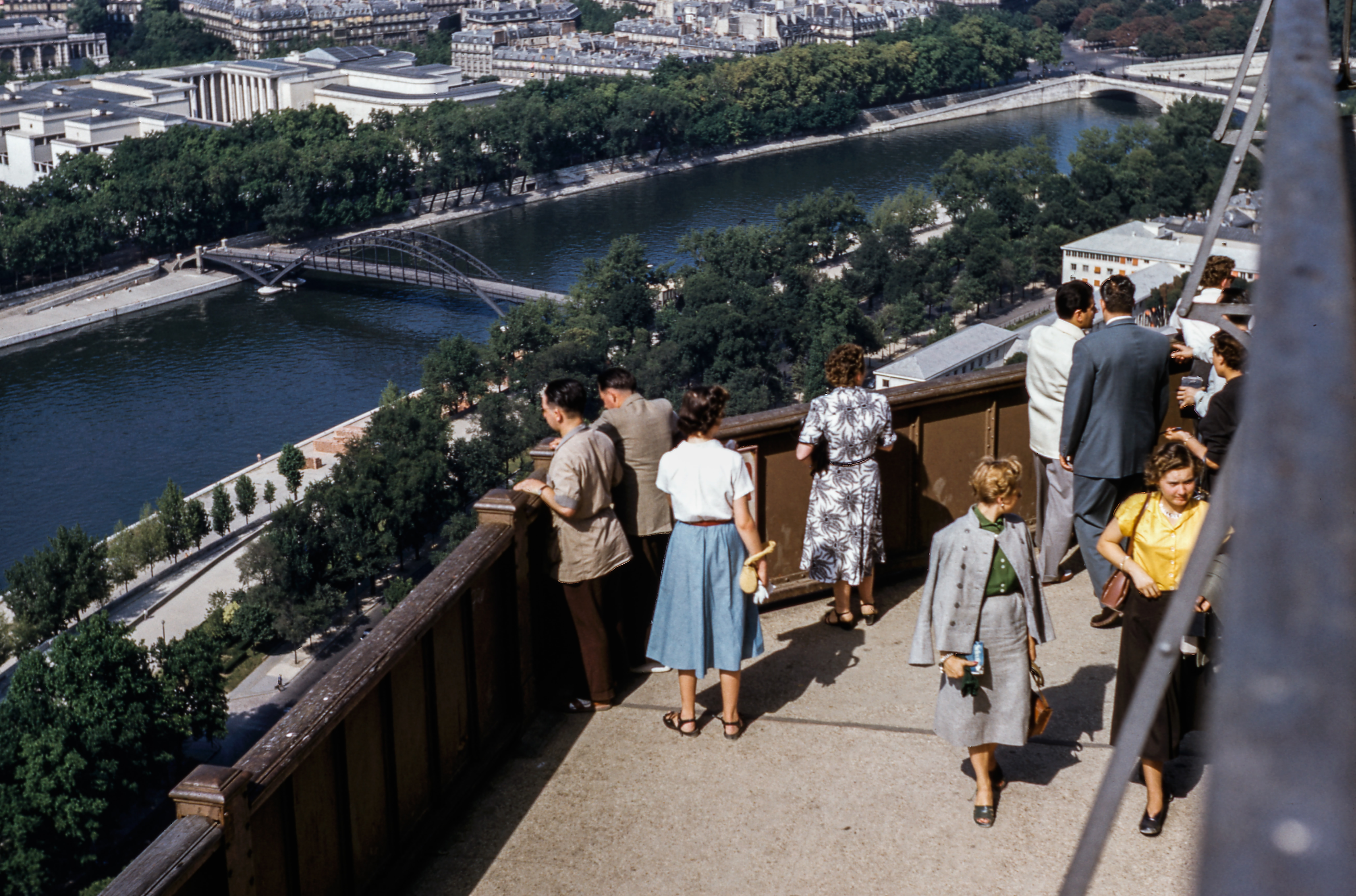 Vintage photo of fashionable tourists looking over the Paris cityscape.