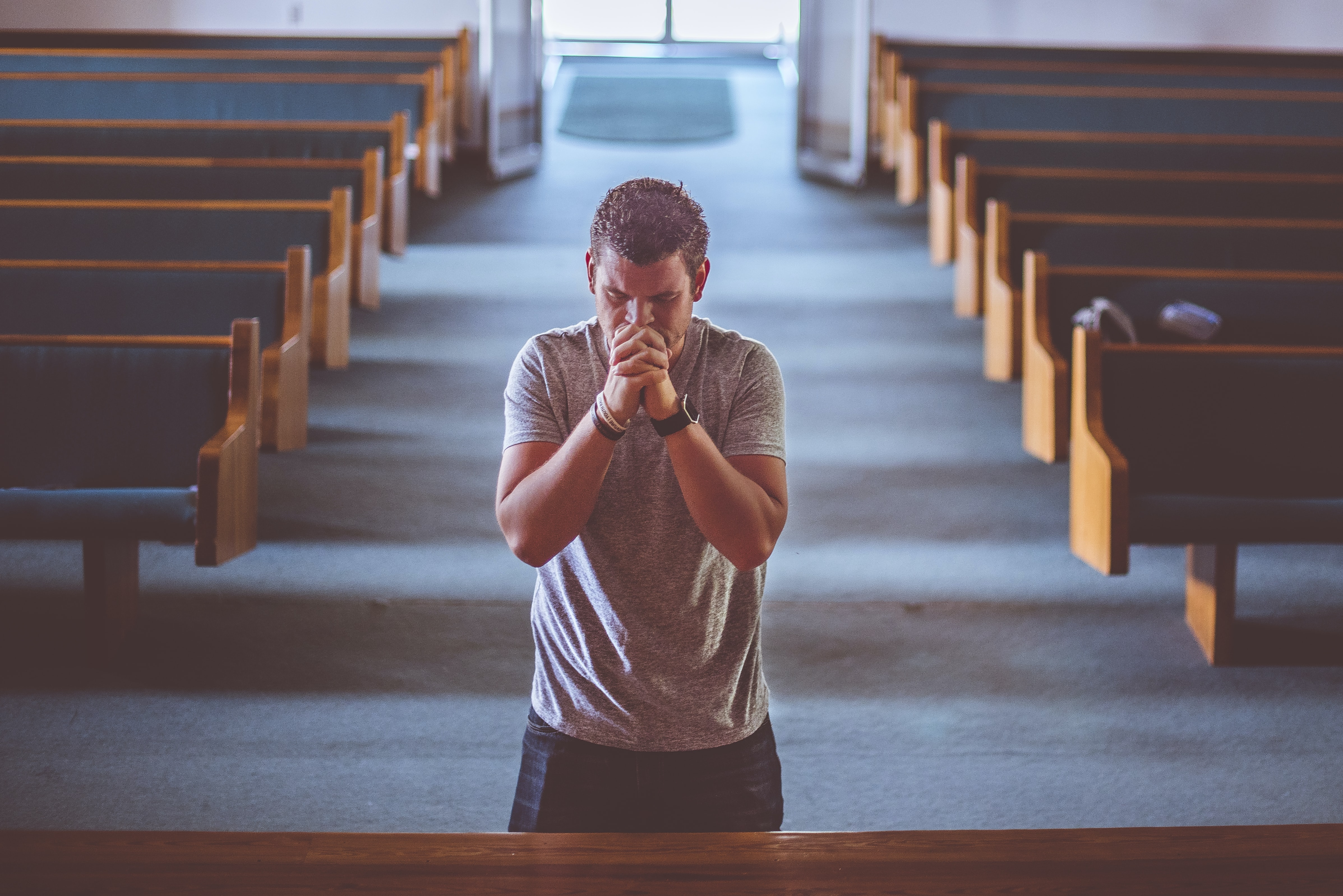 A man praying in a church.
