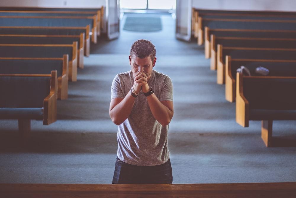 A man praying in a church.