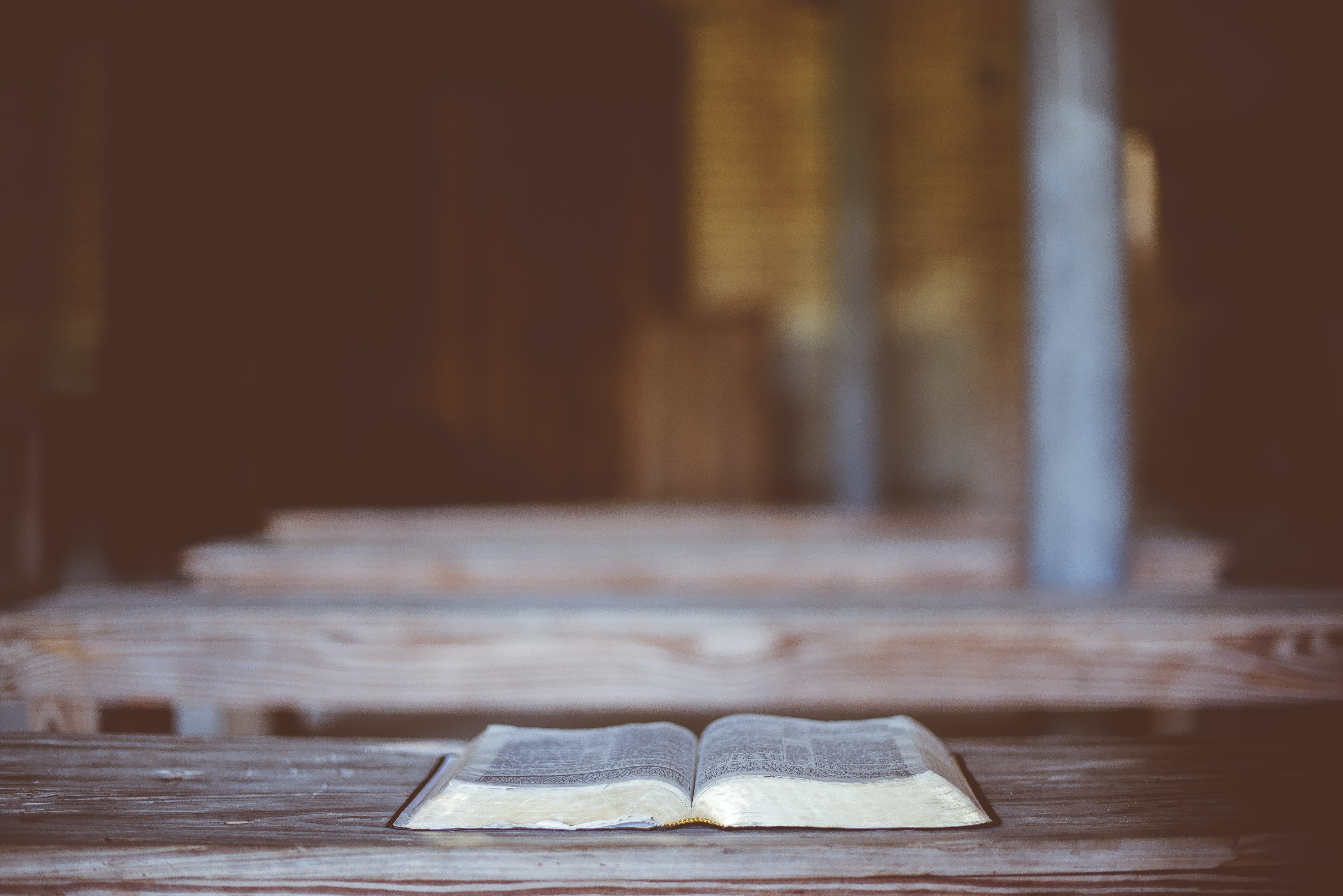 Religious text open on an empty chapel pew