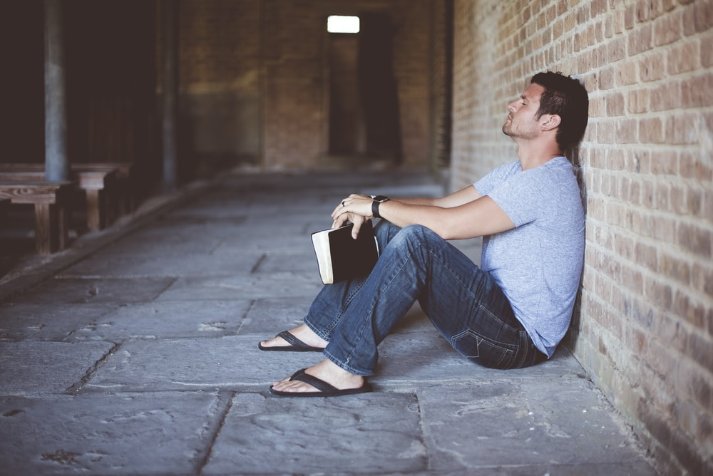 man sitting on pathway holding book at nighttime