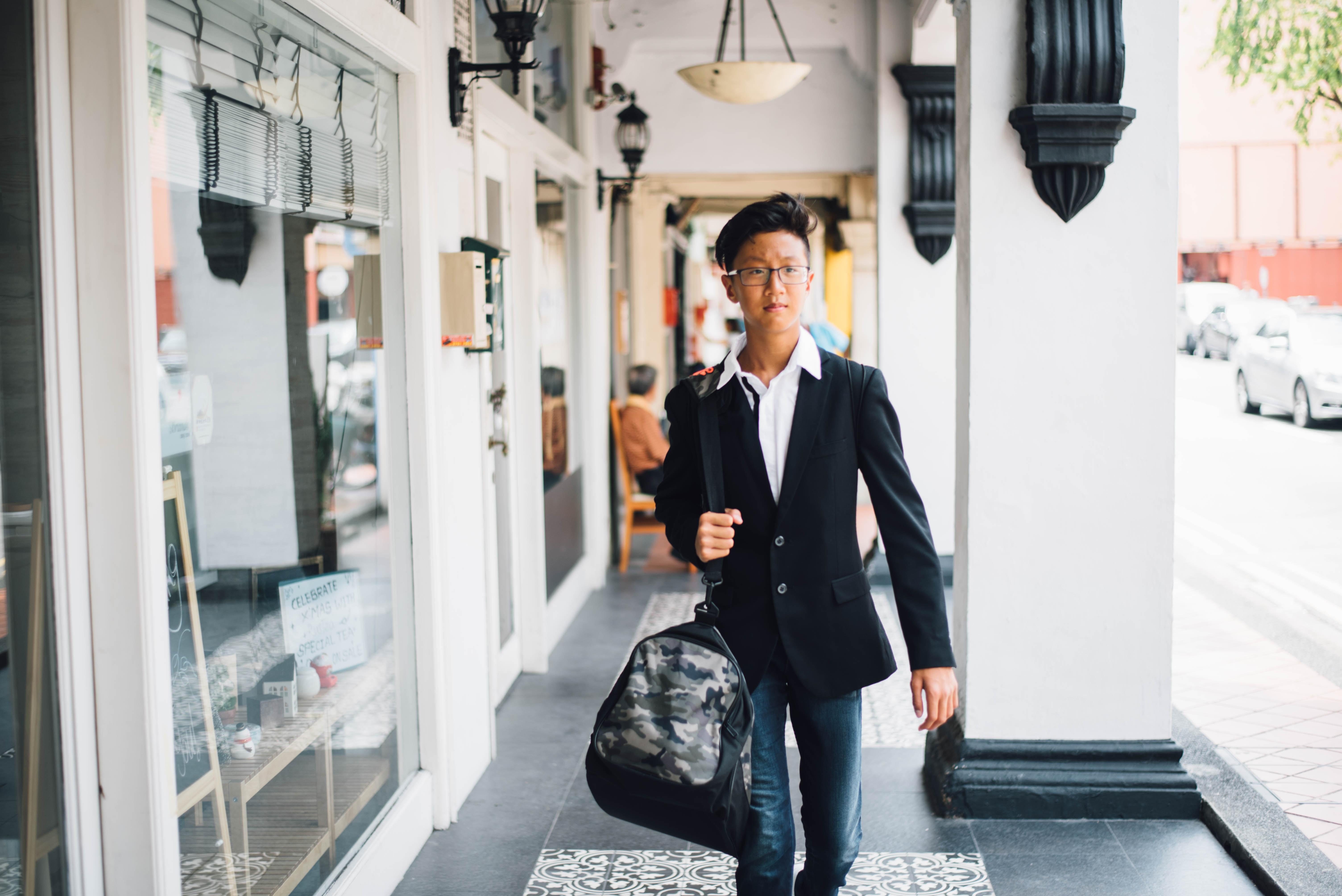 An Asian man walking down the street holding a camouflage duffel bag