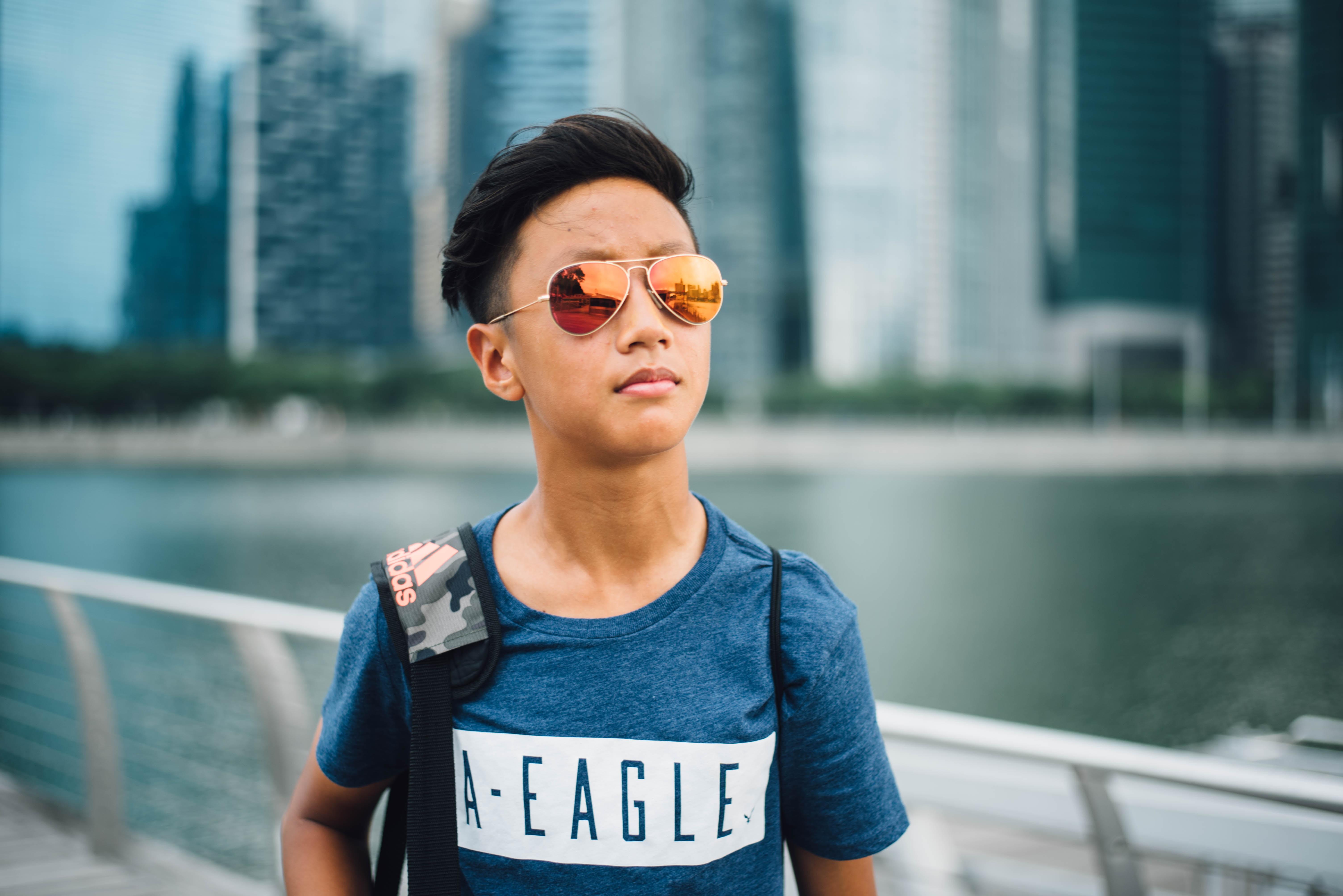 boy wearing yellow lens Aviator sunglasses near gray rail at daytime