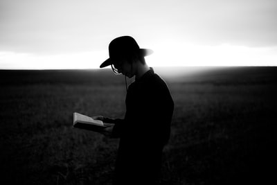 man reading book prairie teams background
