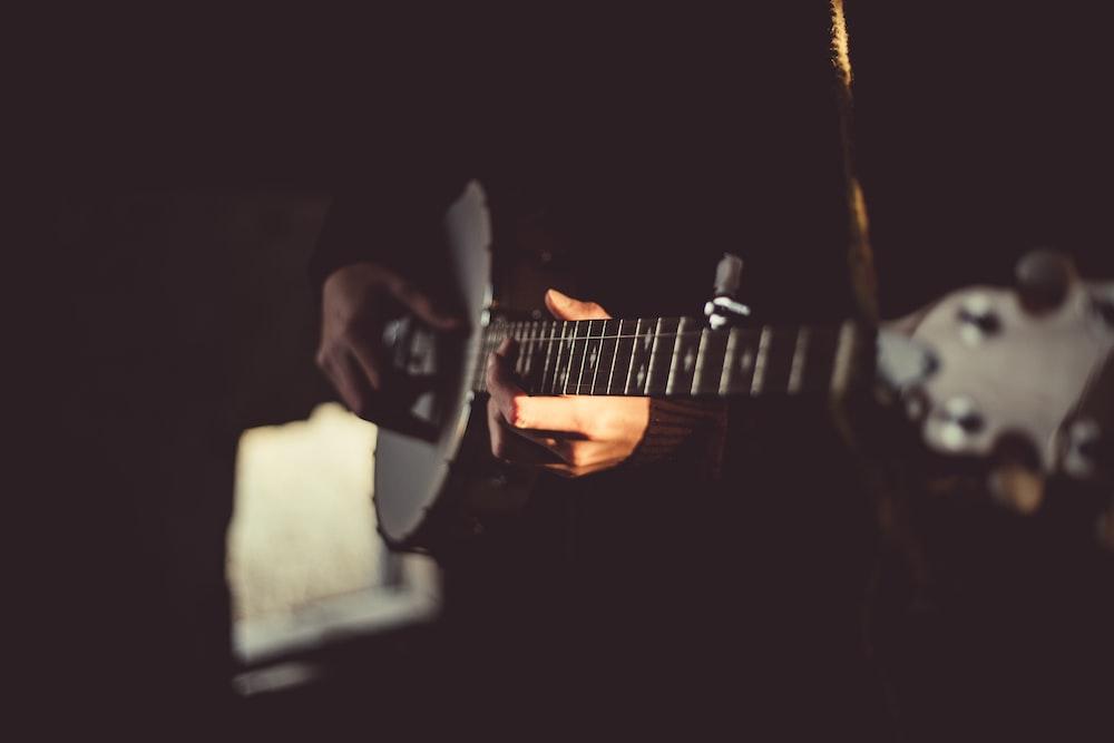 person playing banjo inside dark room