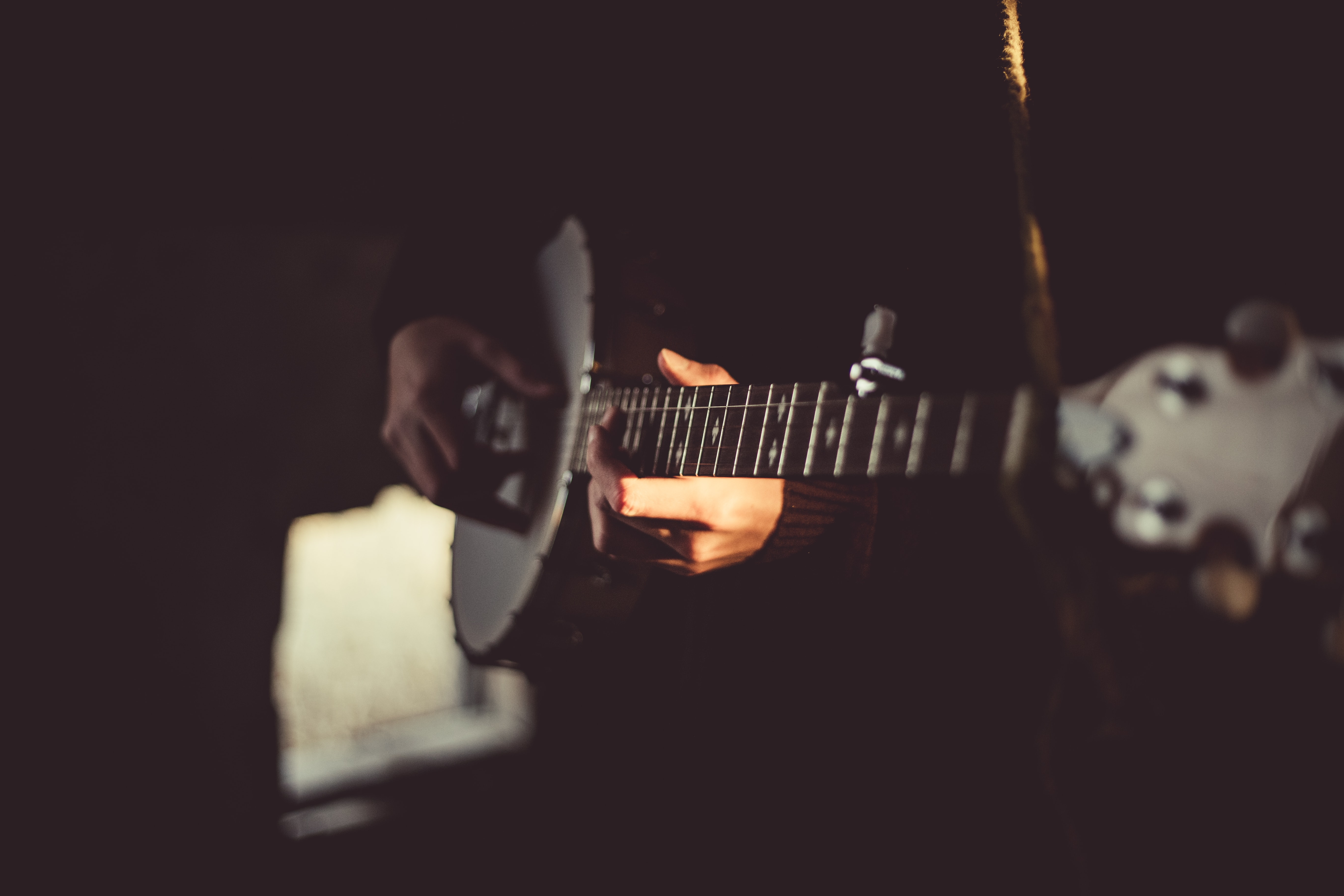A dark, blurry shot of a person playing the banjo