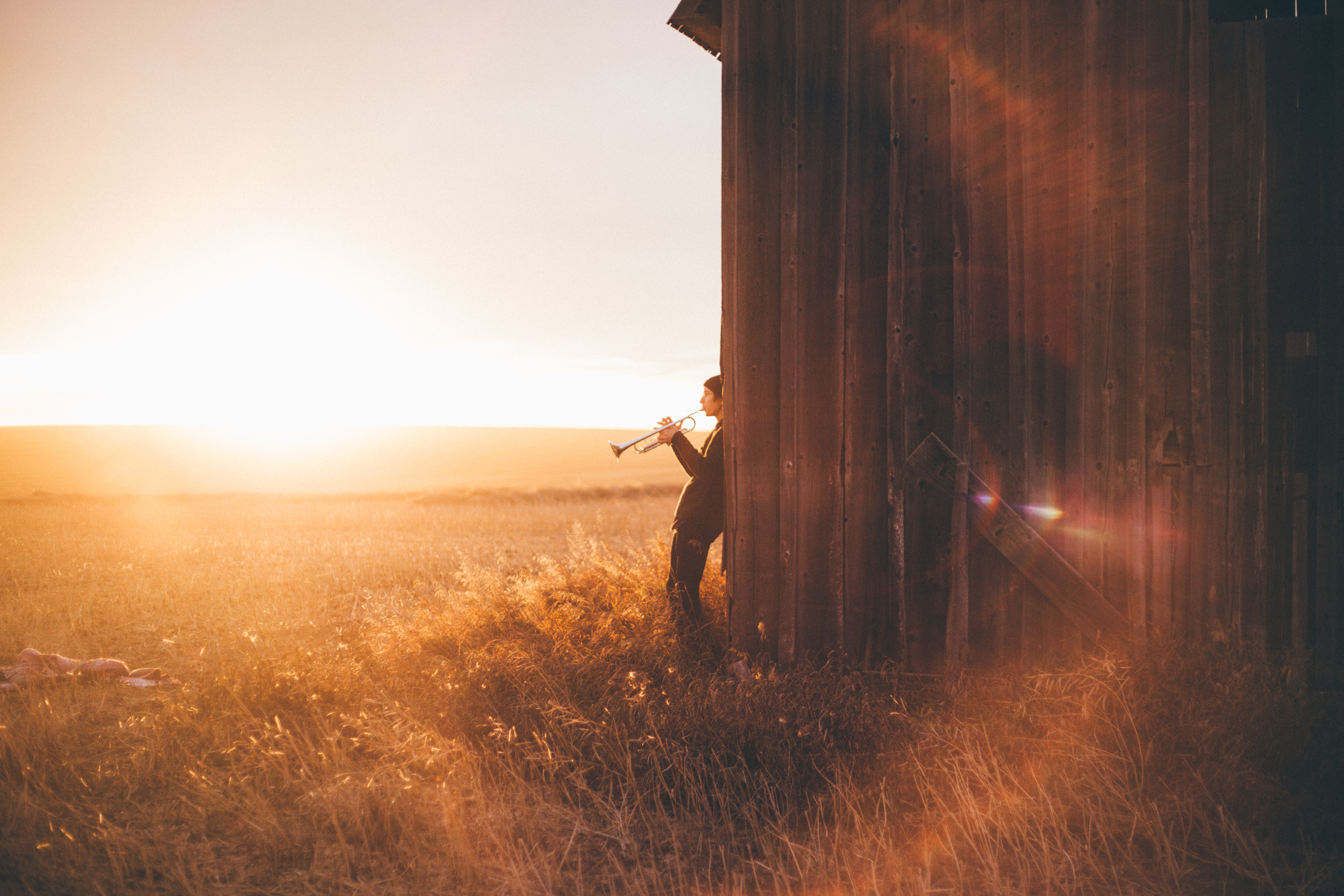 A man plays the trumpet leaning back against a barn wall and facing a golden field