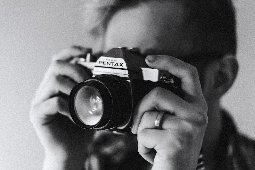 grayscale photo of man taking photo