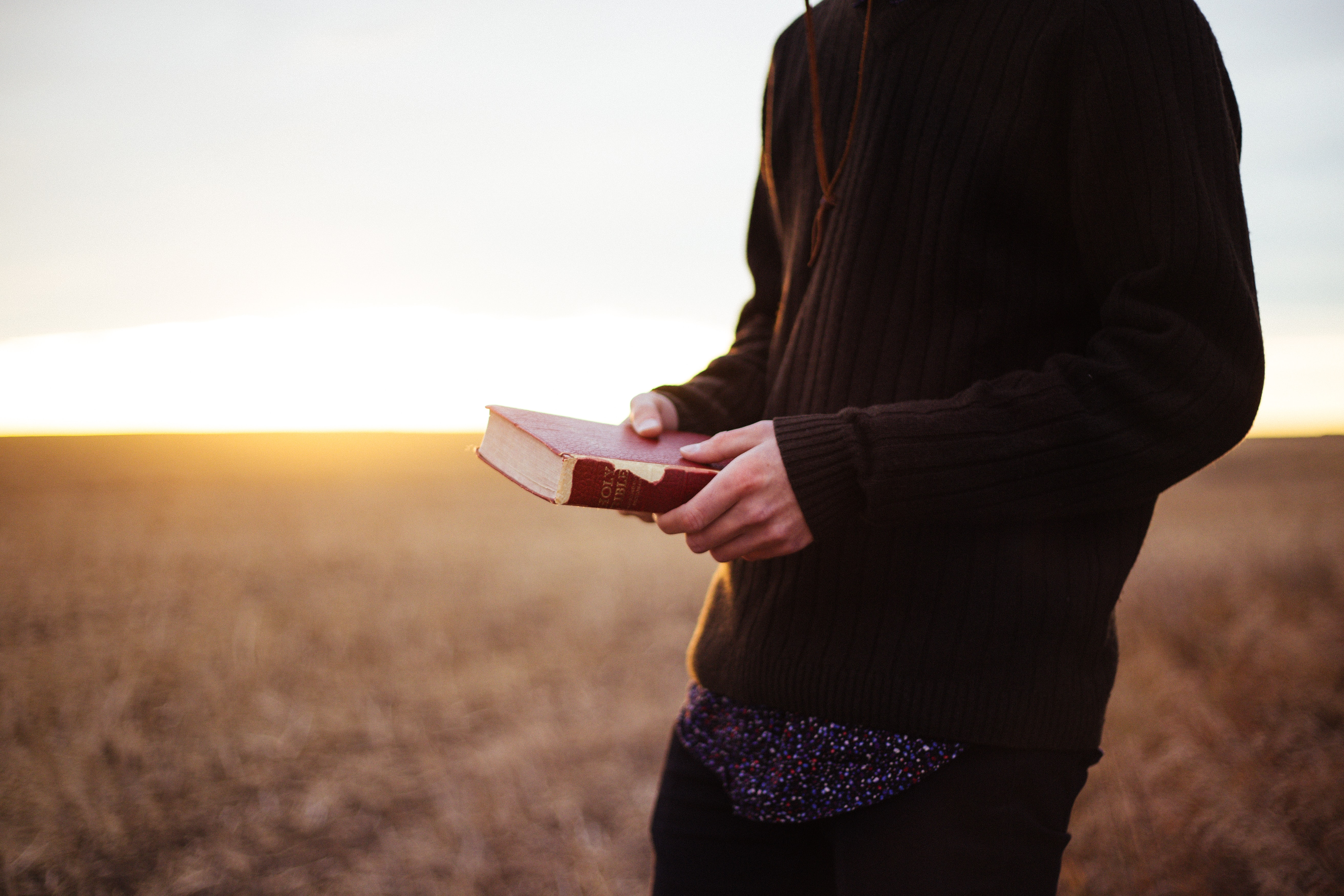 Man in sweater holding bible with two hands in a field during sunset