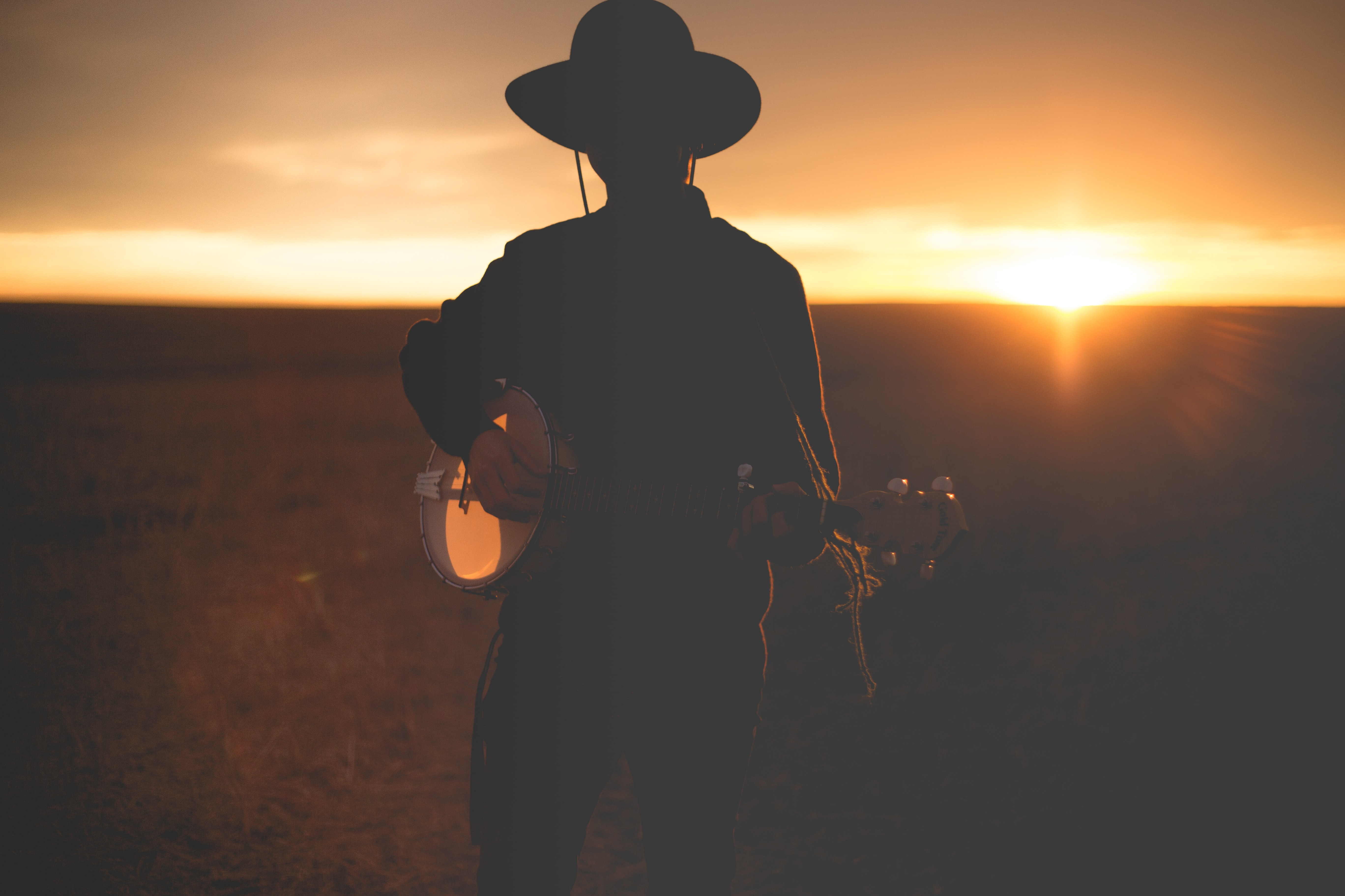 Silhouette of musician with hat playing banjo in field during sunset