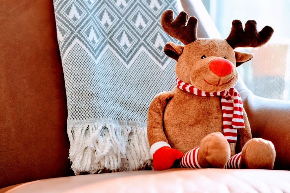 A stuffed reindeer wearing a striped scarf sitting on the couch
