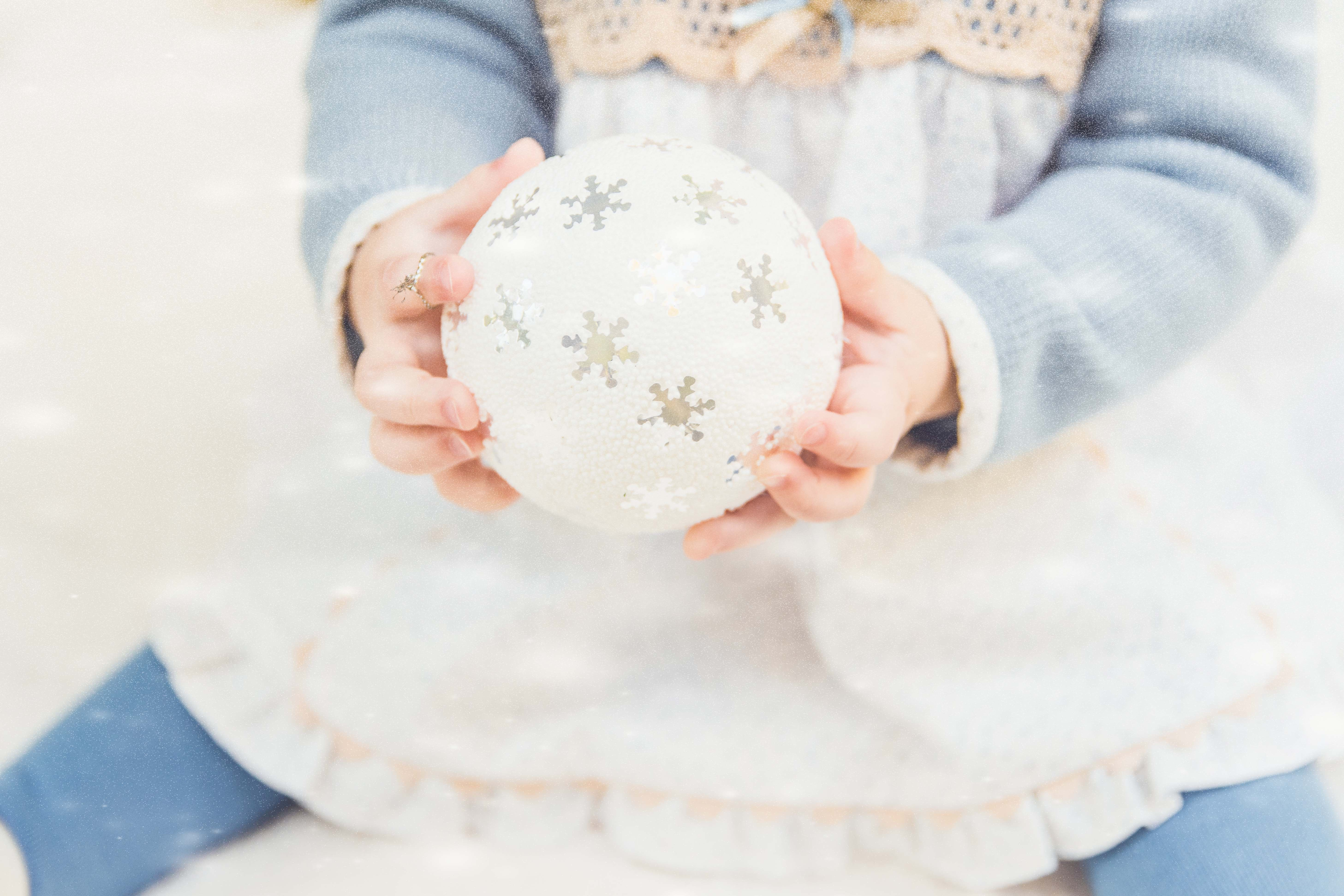 Young child holding a white Christmas ornament decorated with silver snowflakes