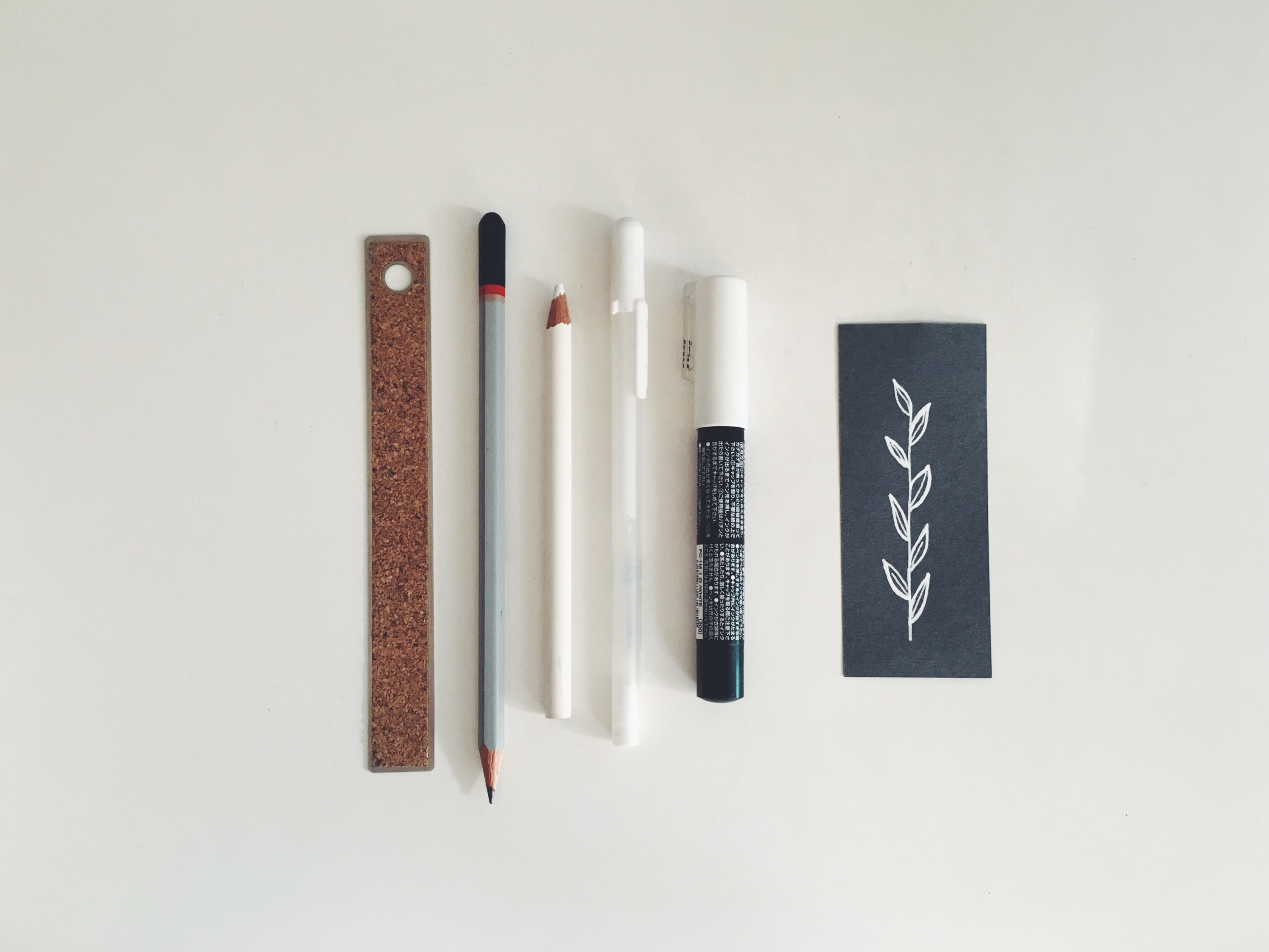 Various pencils, a pen, marker and ruler used to draw a leaf.