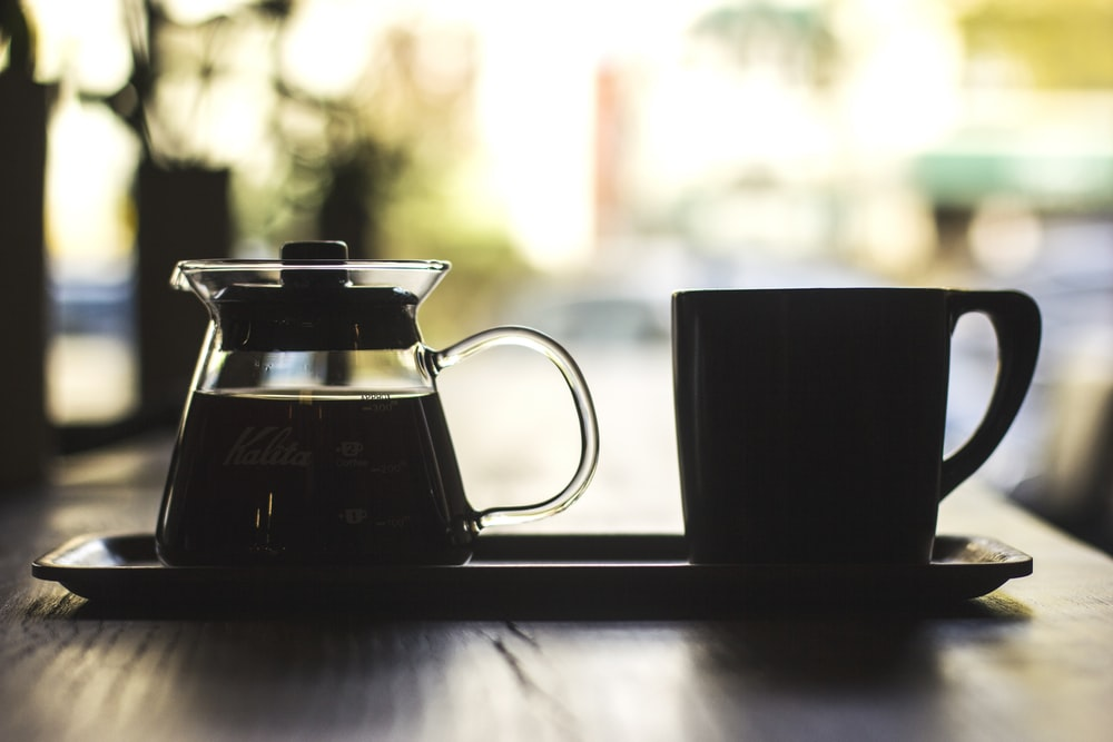 mug and coffee filled carafe on tray at the table