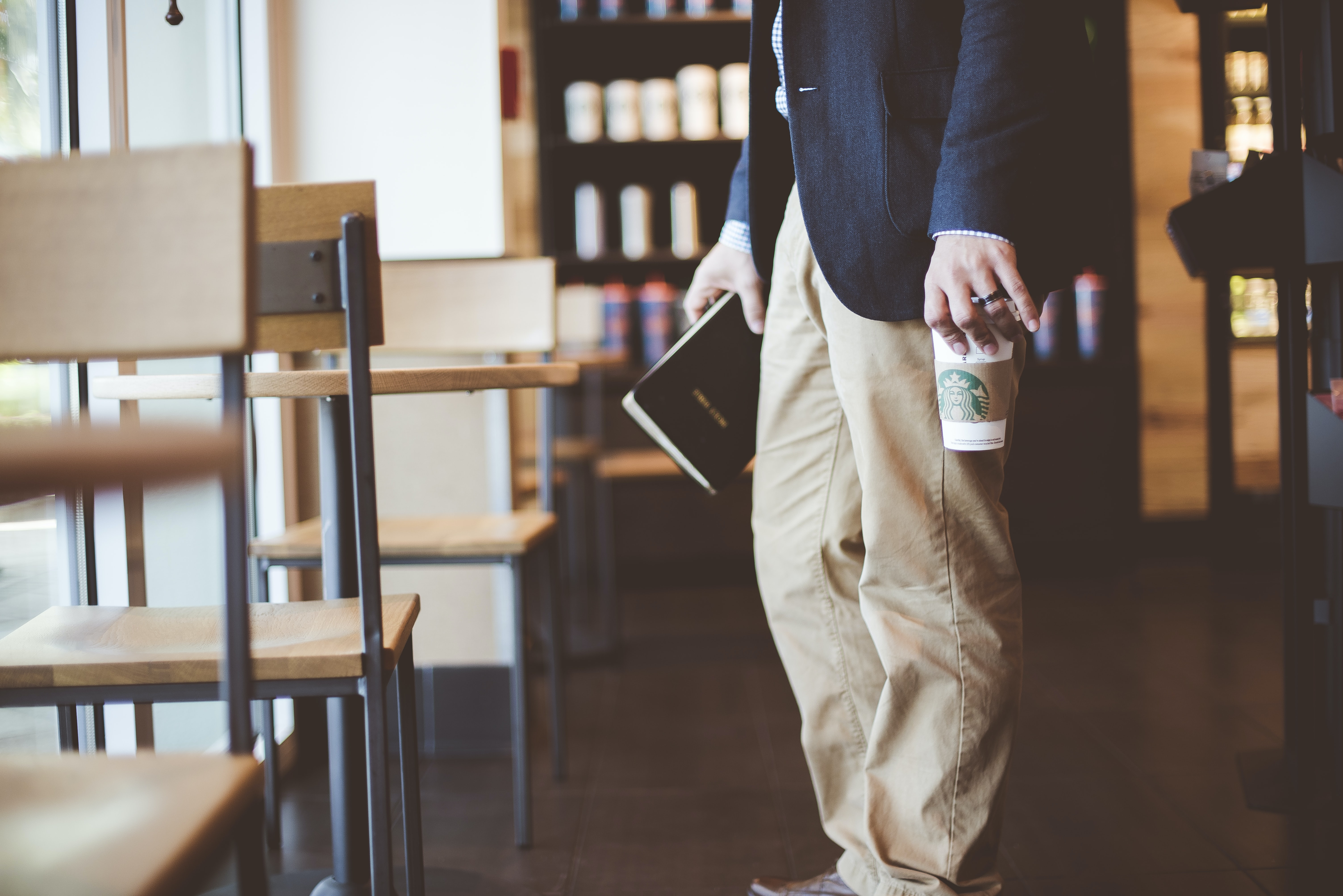 Person in a blazer and business clothes with a Starbucks coffee finding a seat