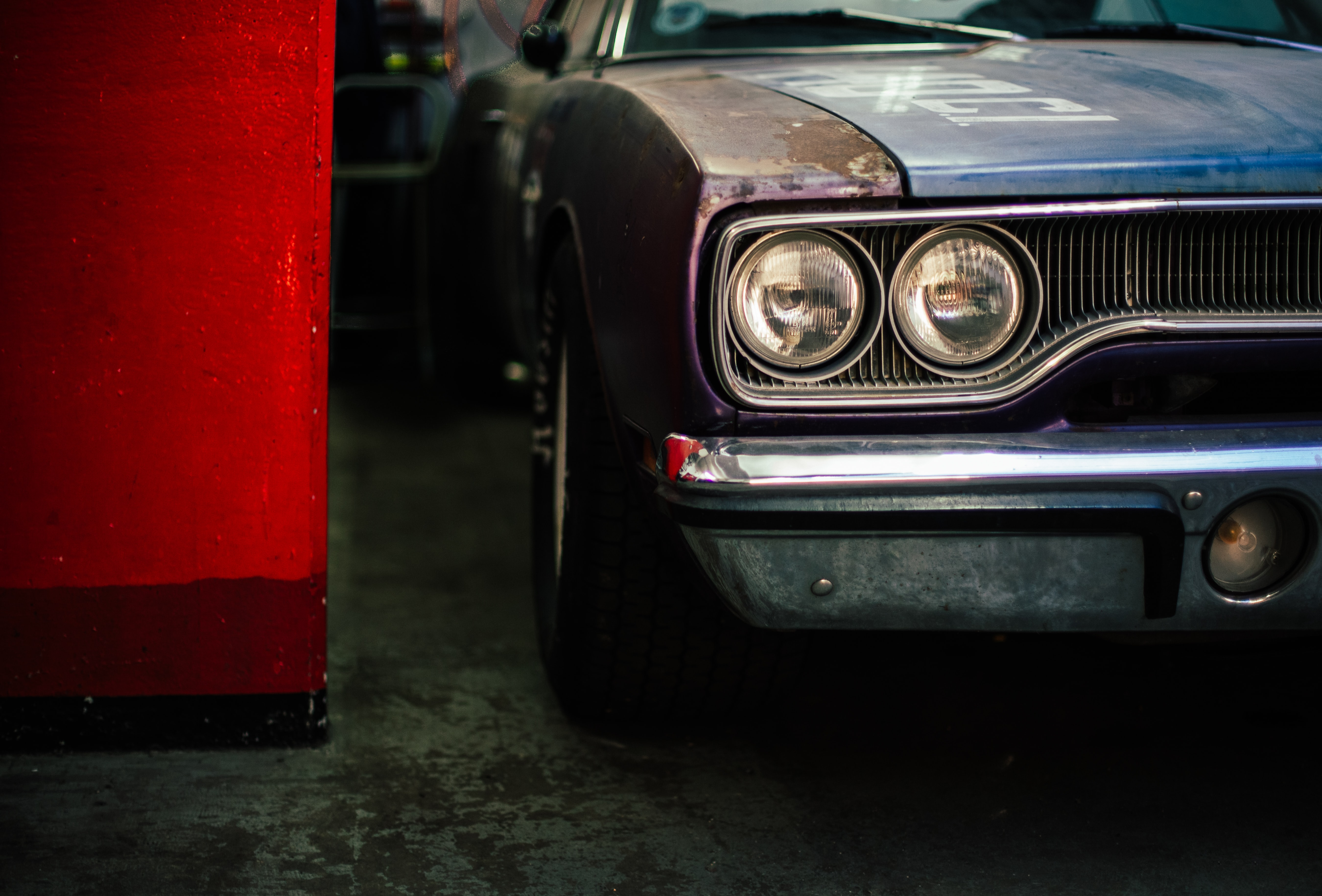 An old, rusted car beside a red wall in a garage