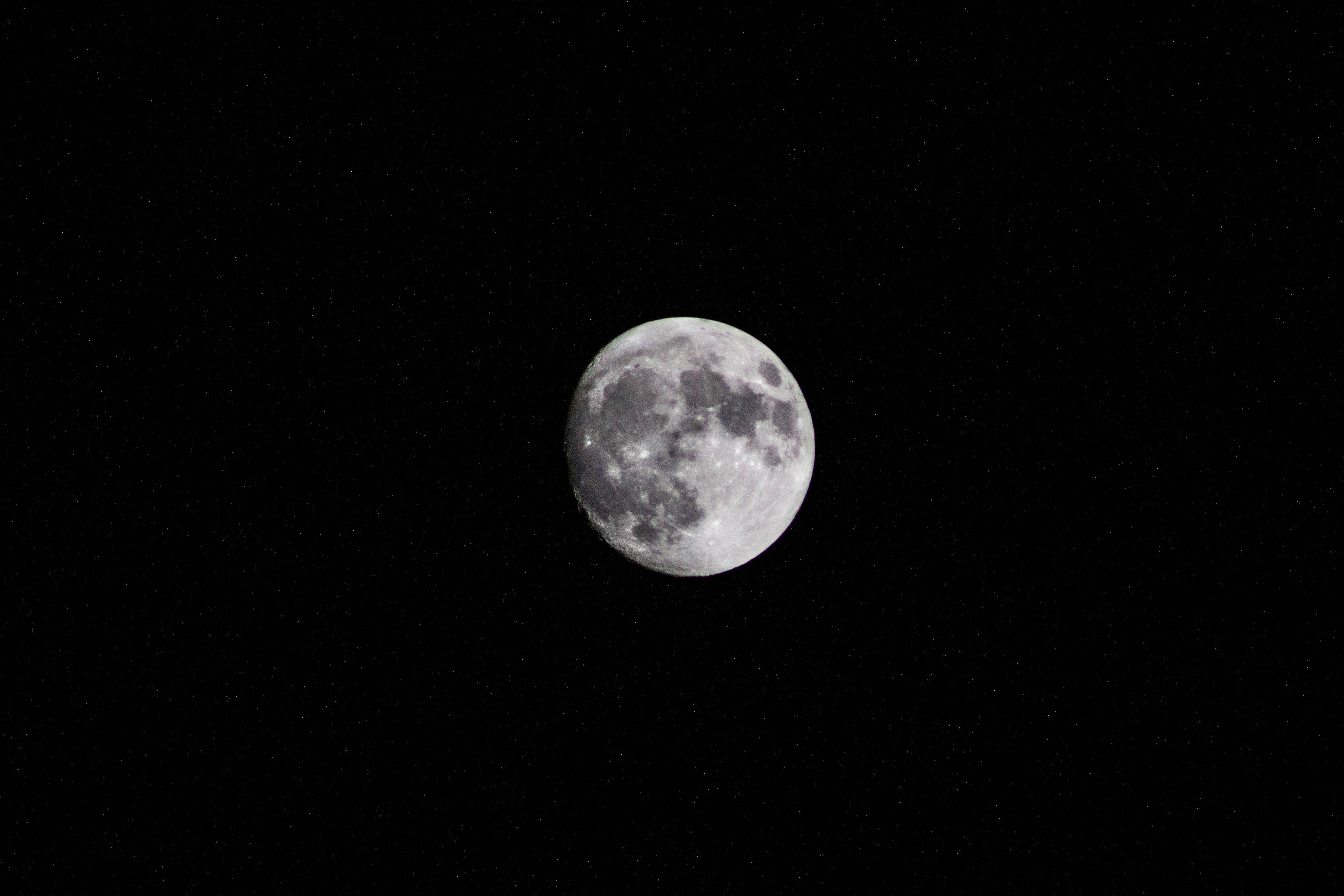 The moon shines against a pitch black sky at night