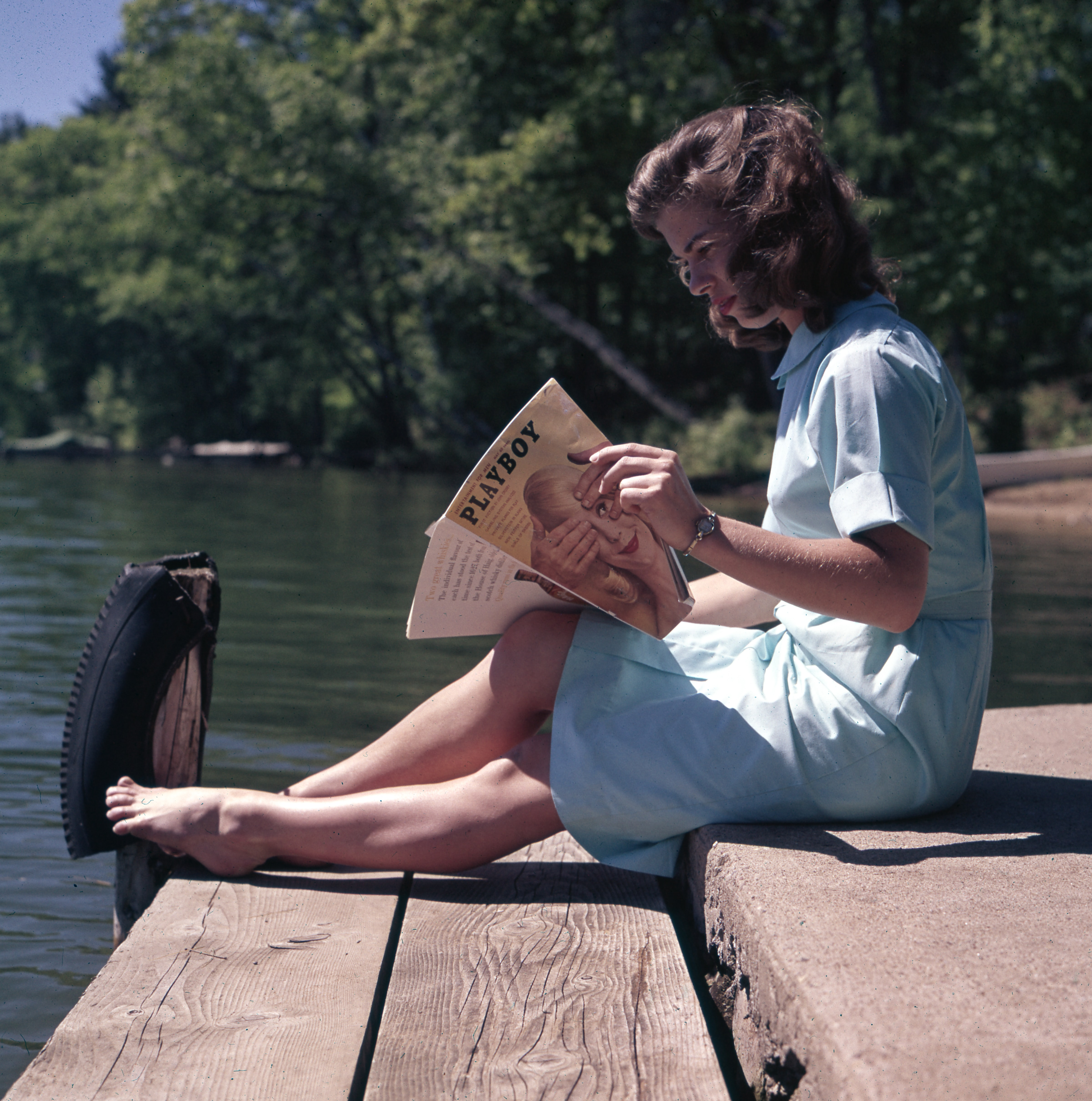woman sitting while reading near body of water
