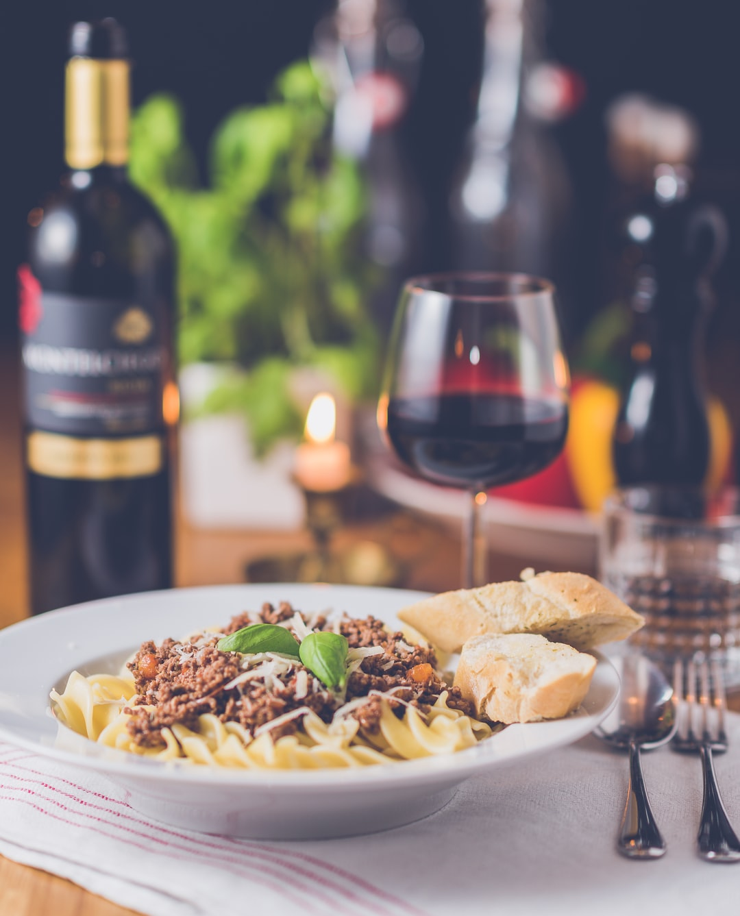 A plate with a pasta dish next to a wine bottle and a glass of red wine on a set table