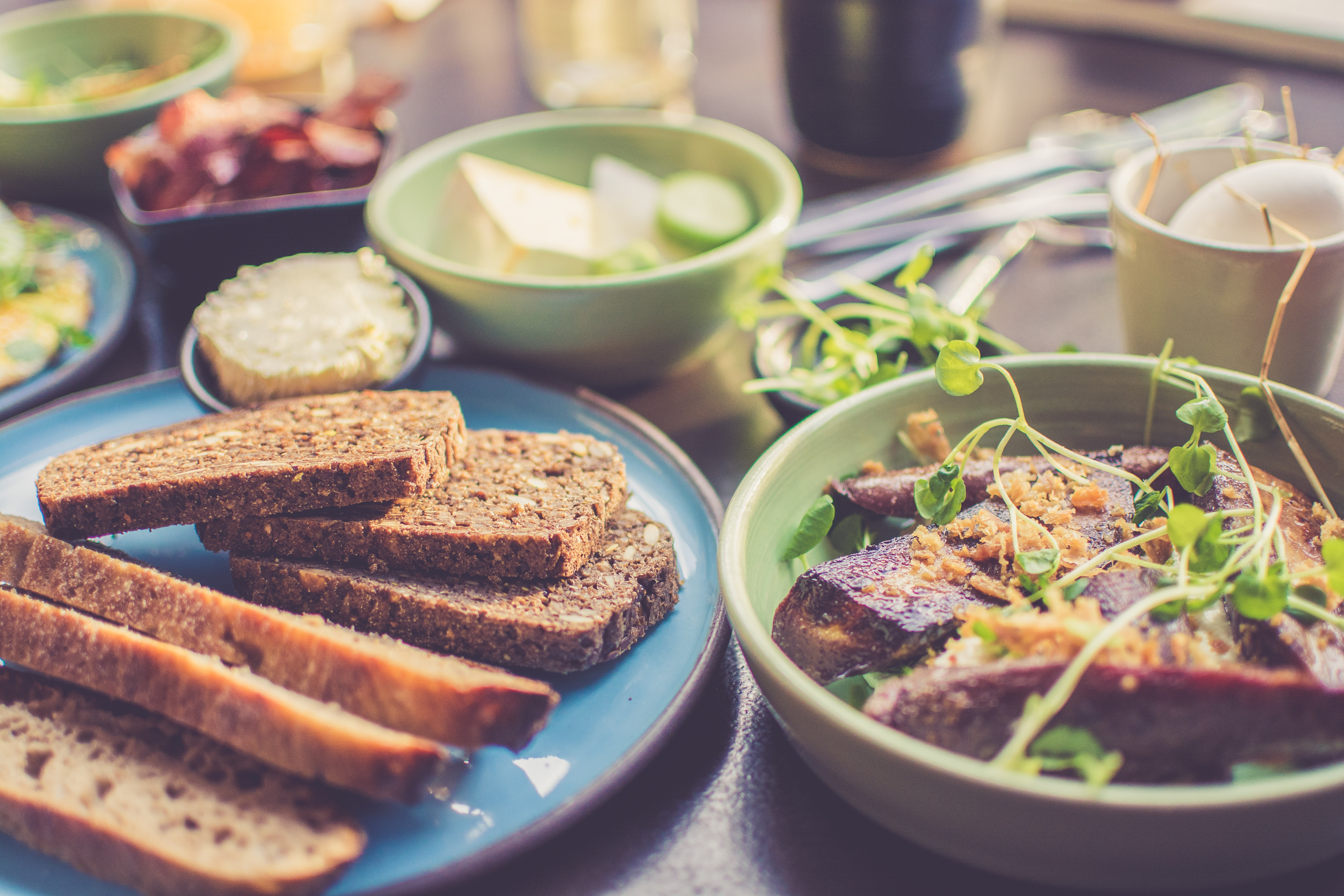 Kitchen table with slices of bread, meat with herbs, and fruit