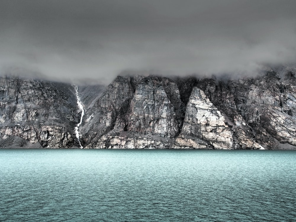 gray cliff beside body of water covered by fog