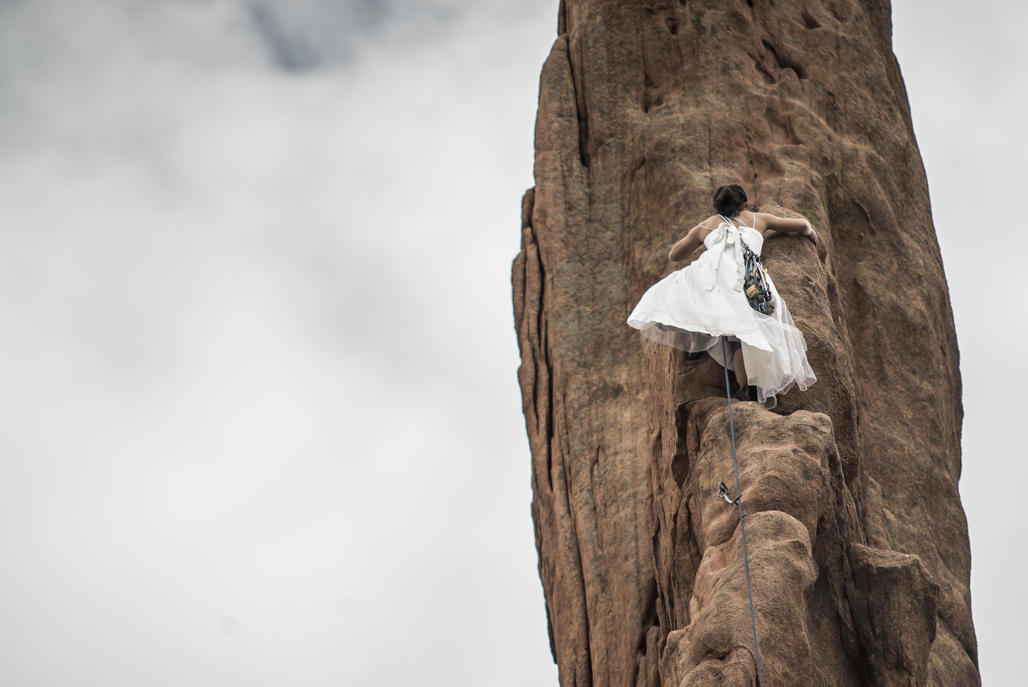 woman wearing white wedding dress climbing on brown rock under white sky