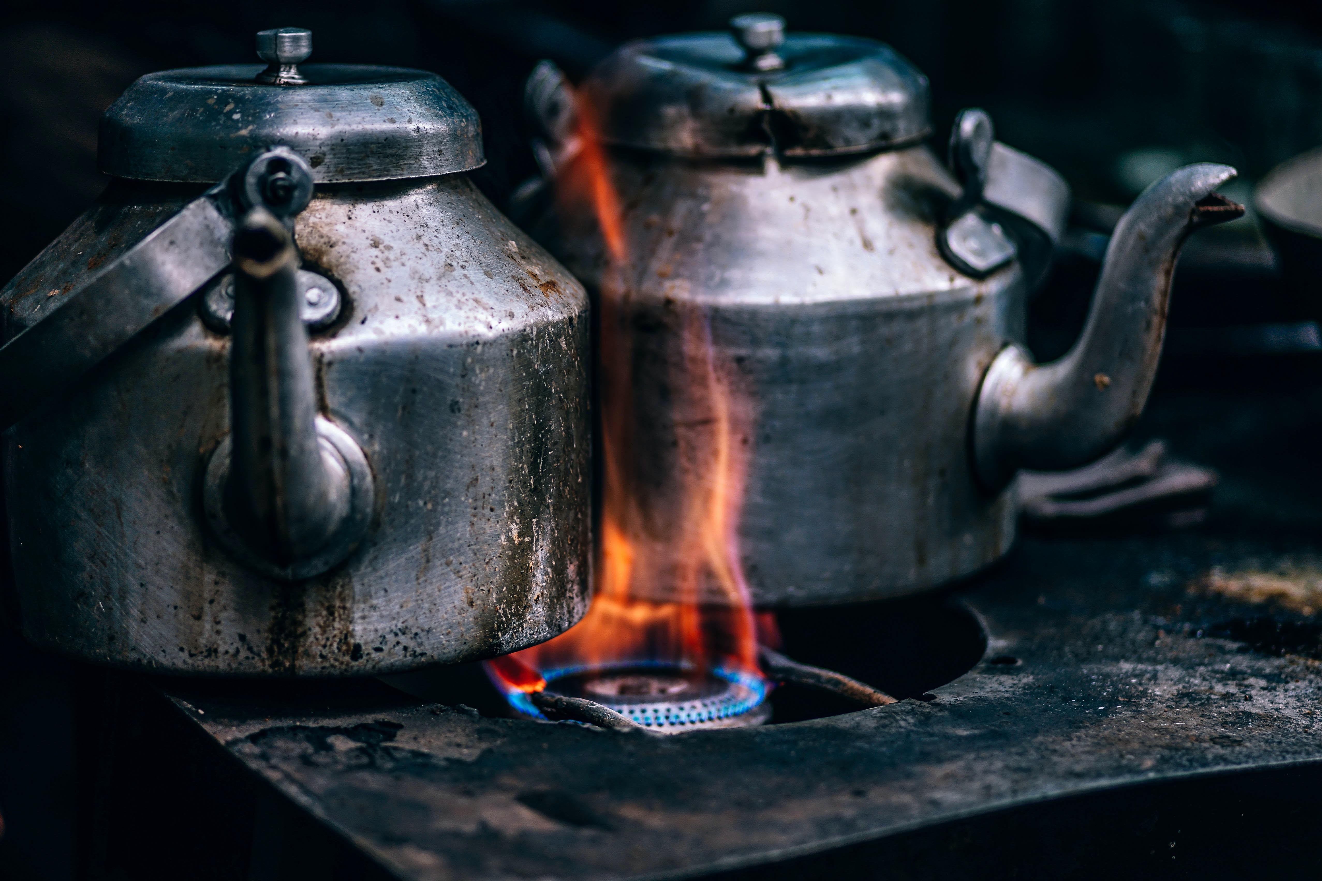 Rustic metal tea pots on an open flame