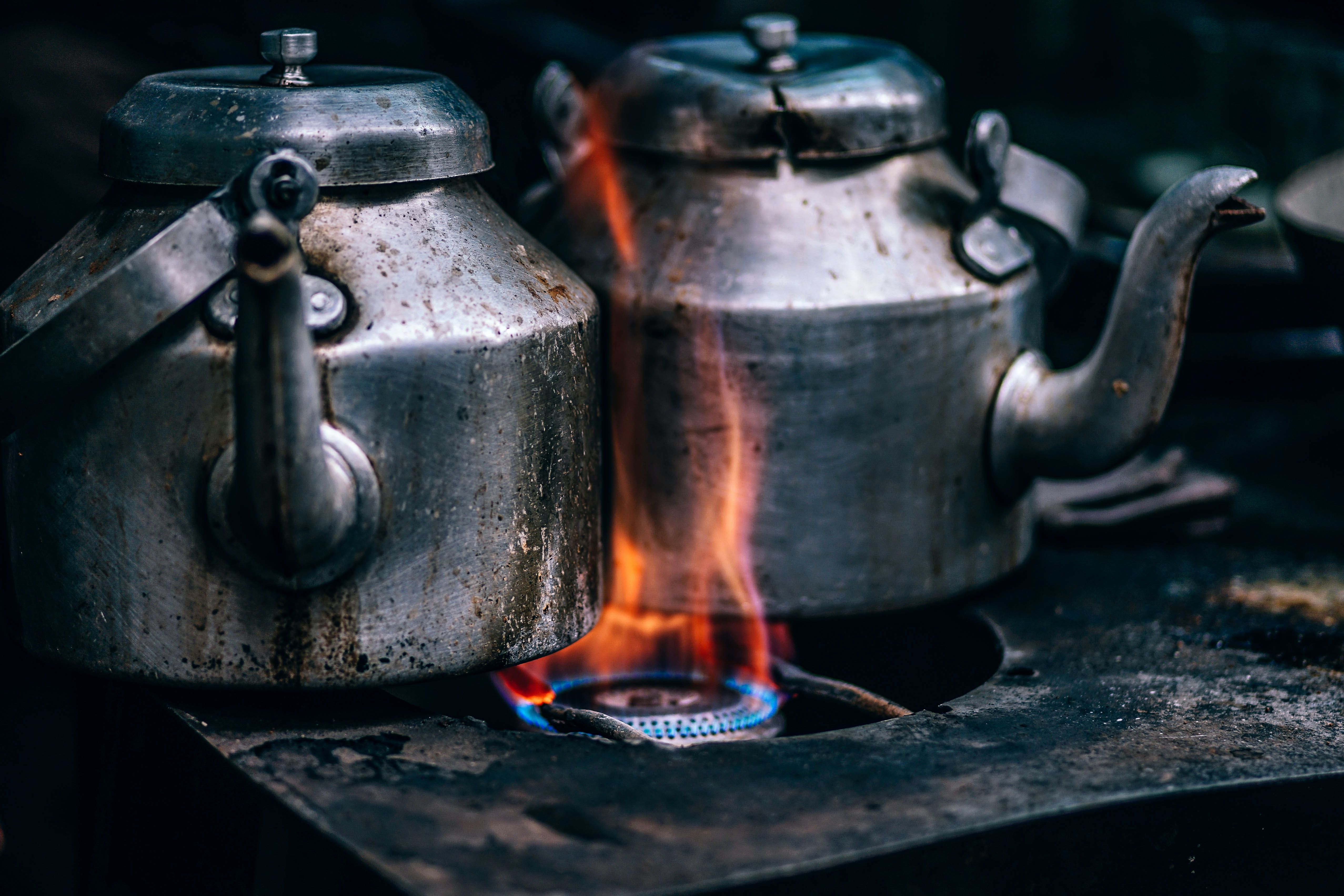 Rustic metal tea pots on an open flame