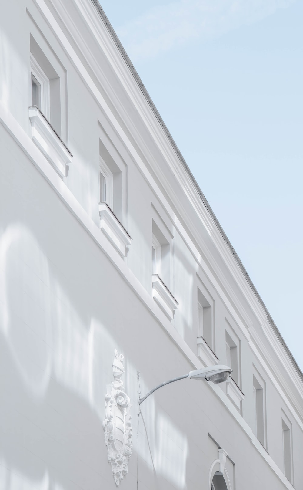 white street lamp mounted on white building wall