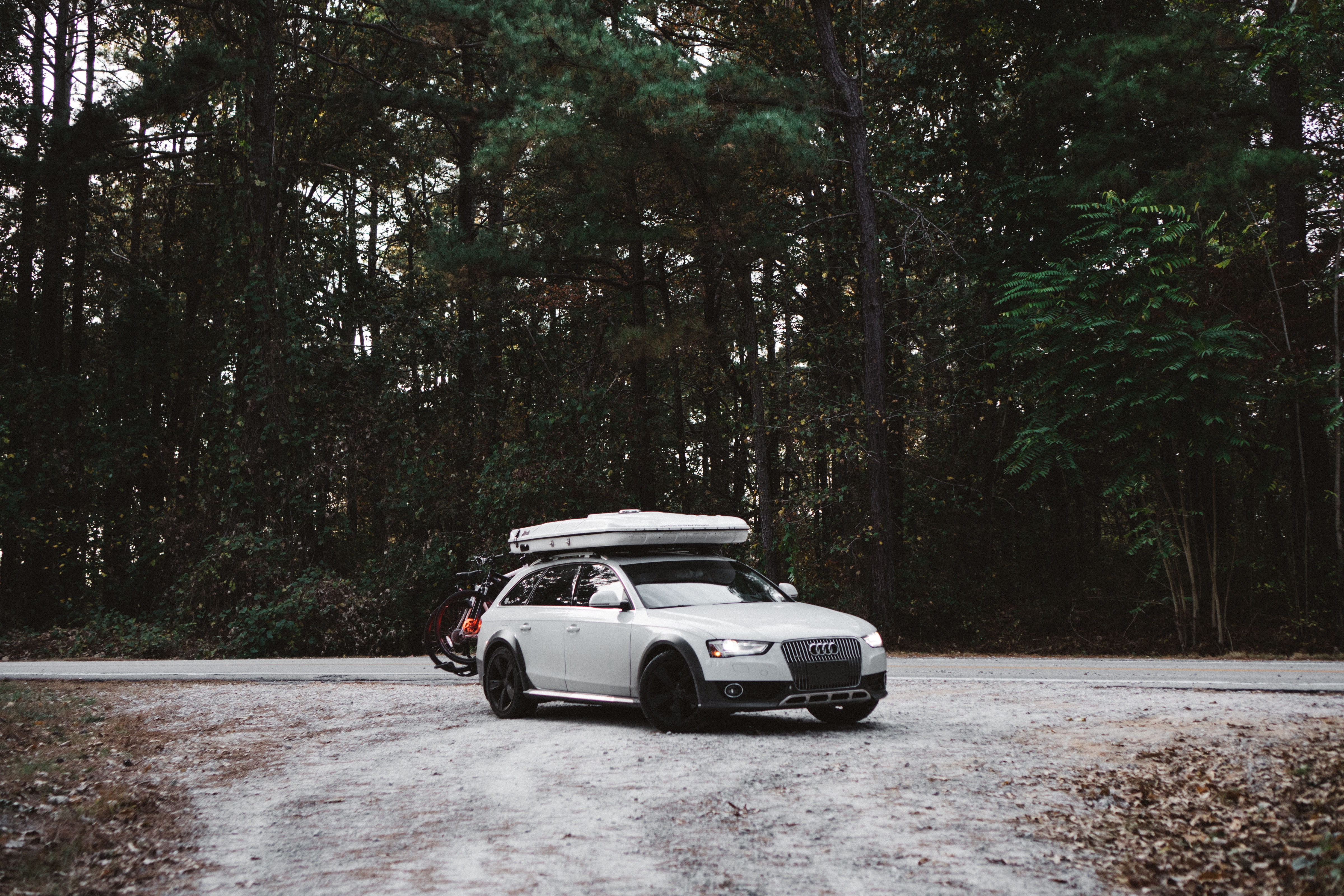 White Audi SUV in a campground with luggage on the roof.