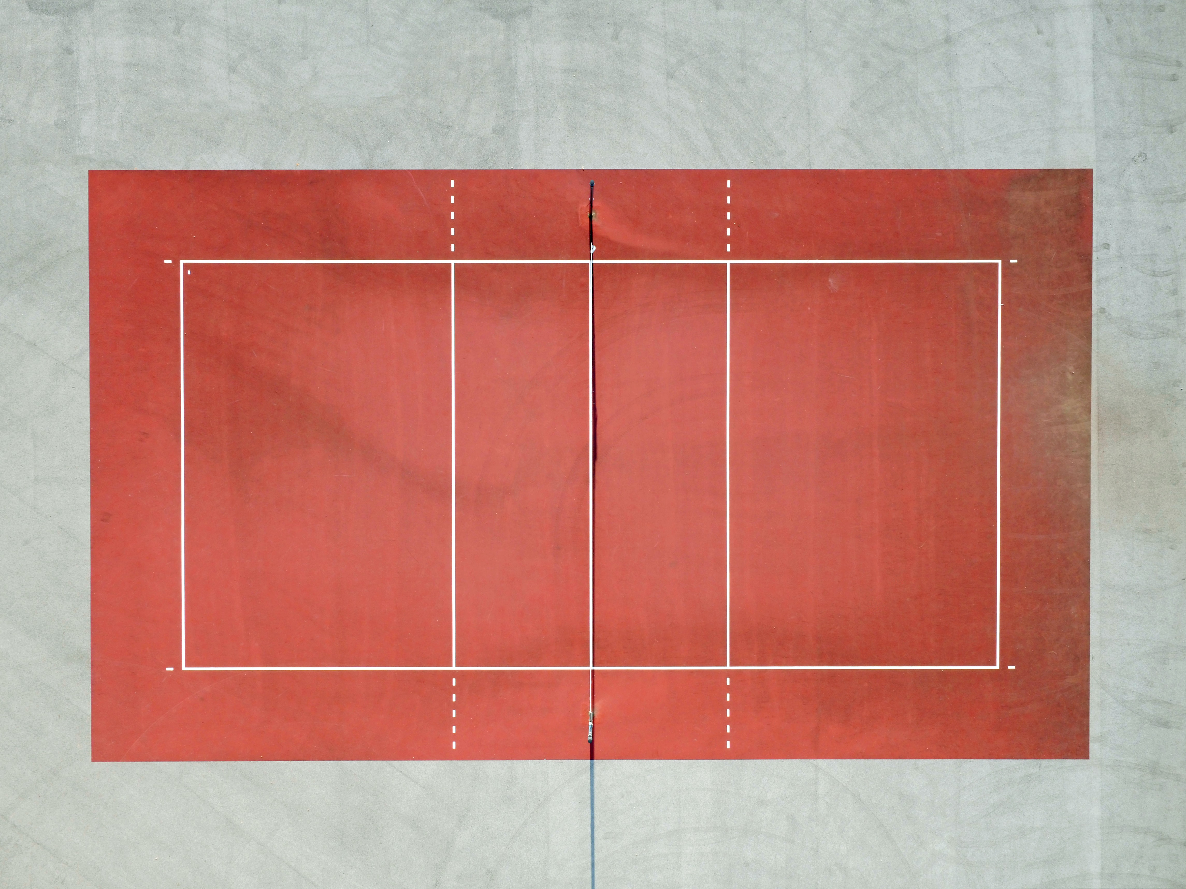 A drone shot of a red tennis court