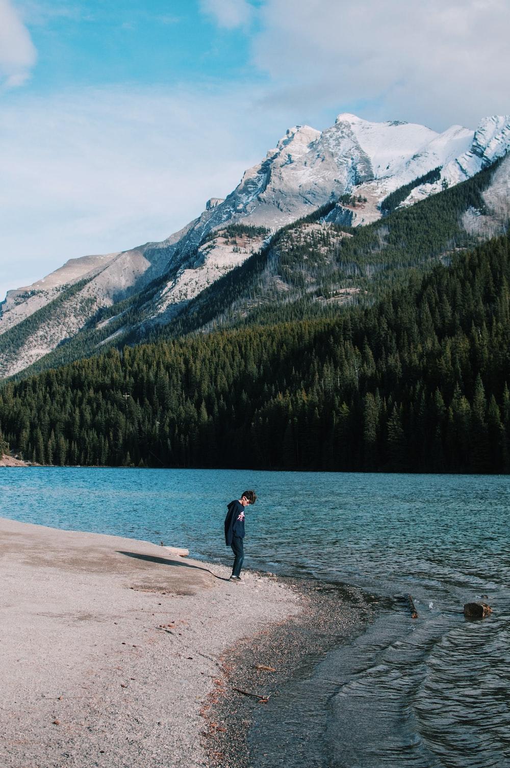boy standing in seashore beside body of water