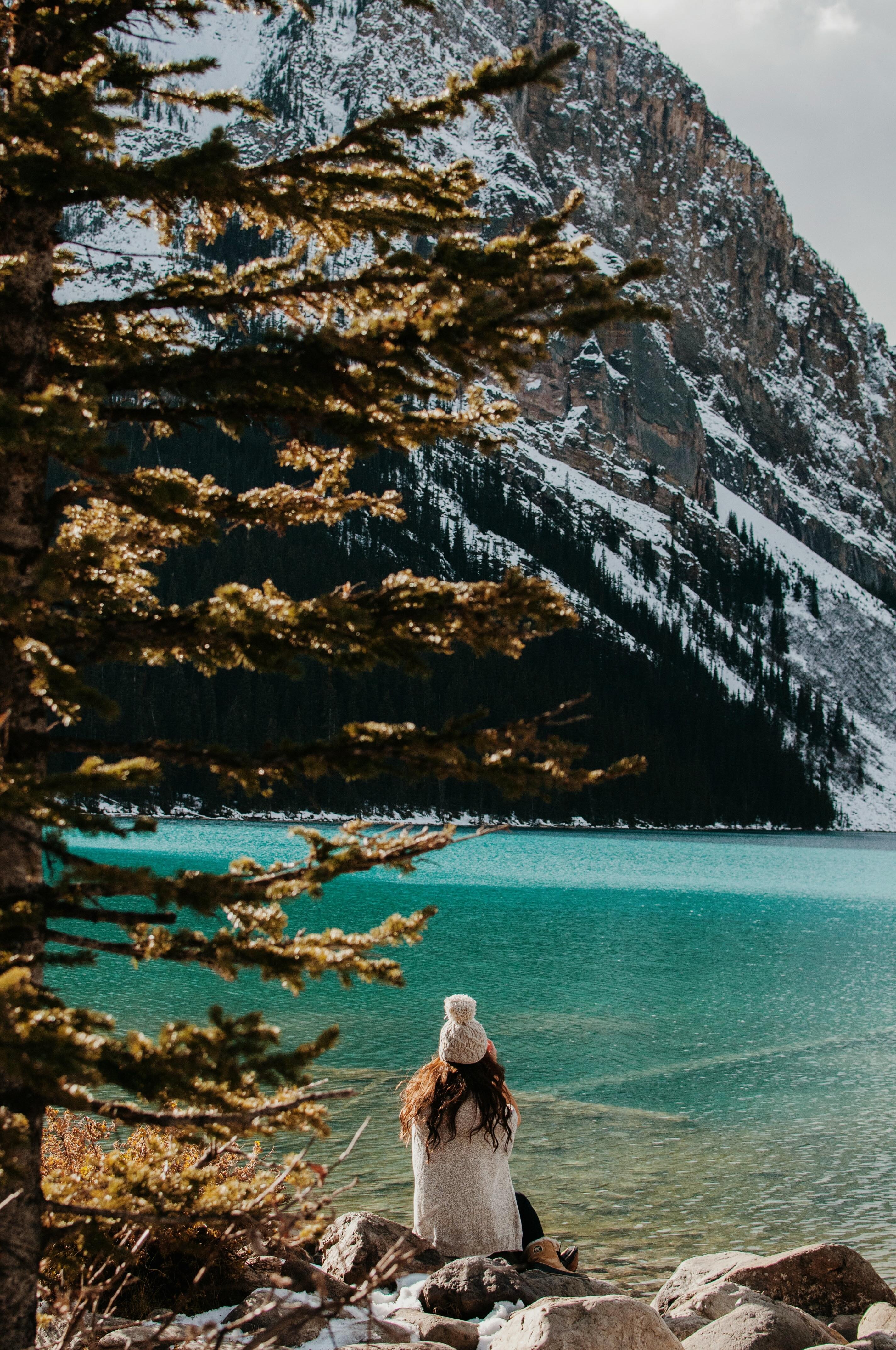 A woman in a knit cap sitting on rocks on the shore of Lake Louise