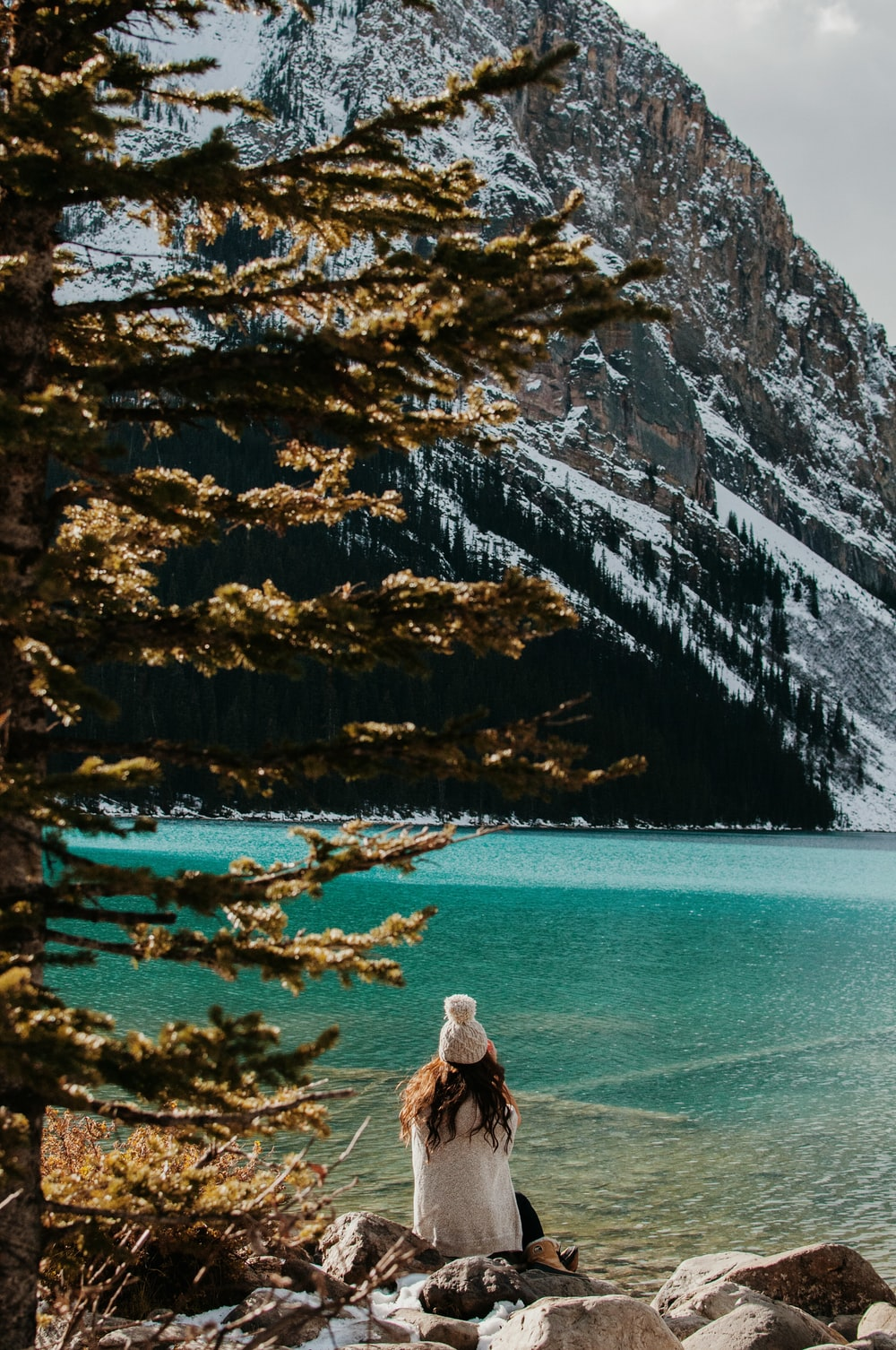 woman sitting on stone facing body of water and glacier mountain during day