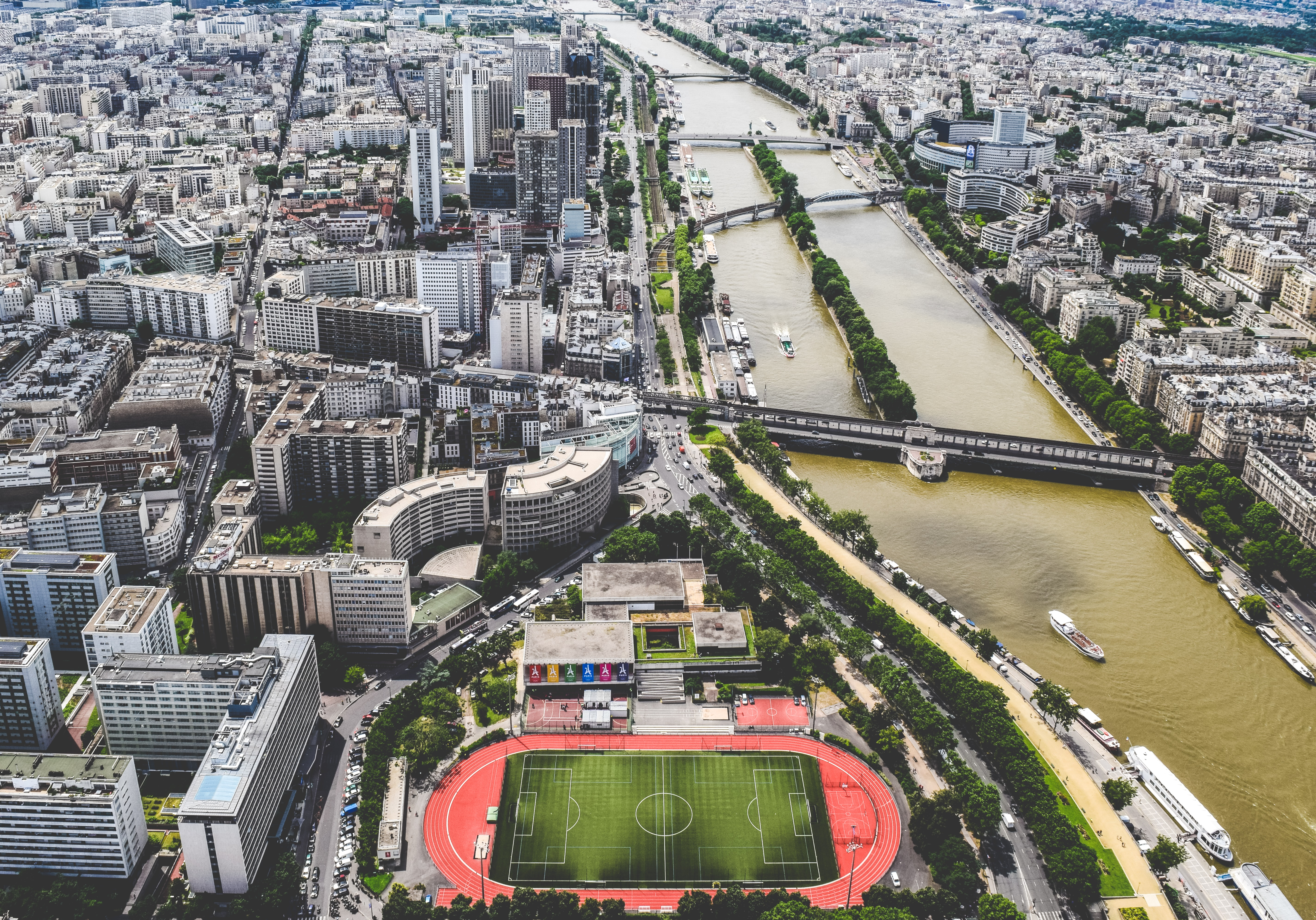 Drone shot of Paris showing skyscrapers, a soccer and track field, and boats on river Seine